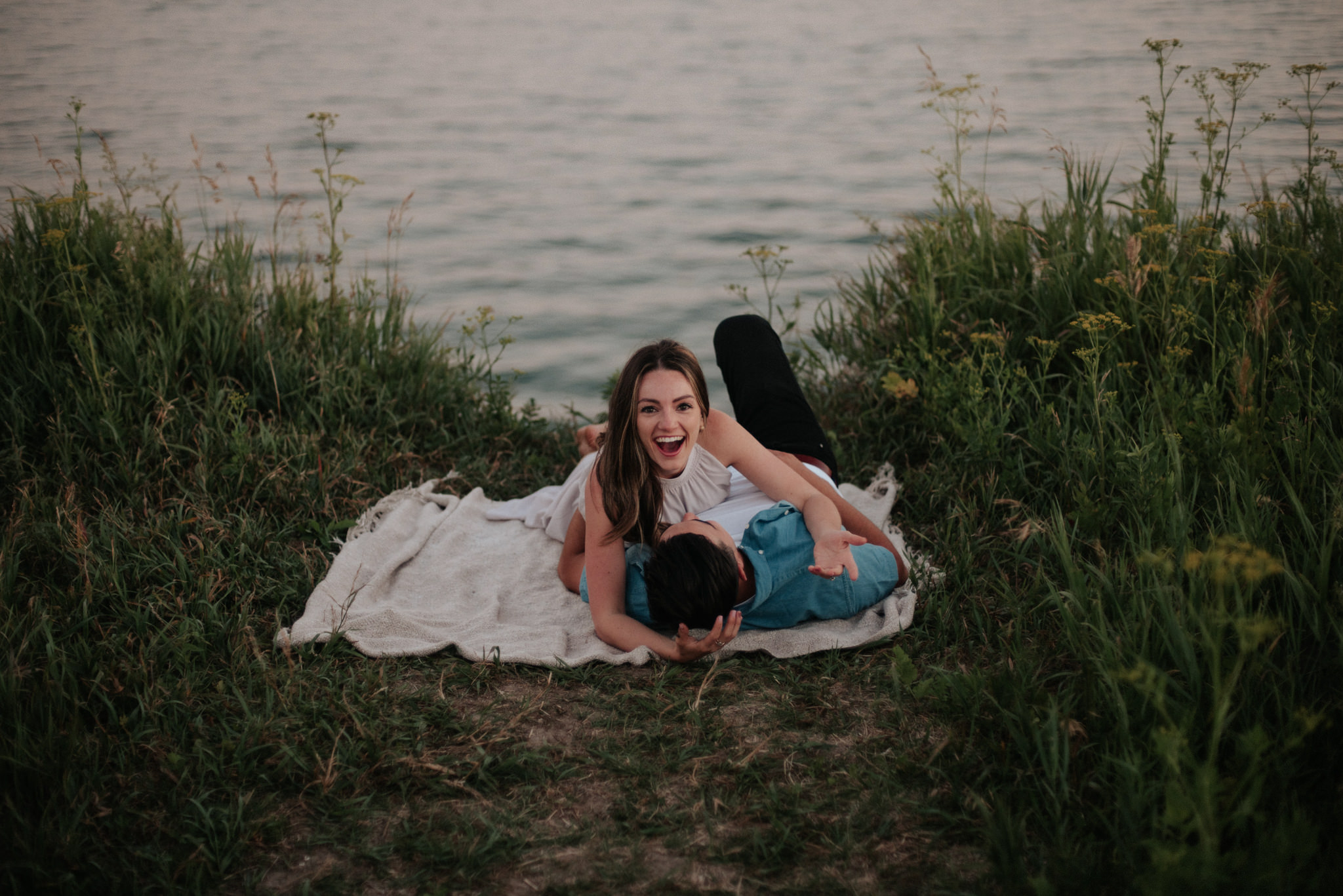 couple lying down facing each other at engagement shoot
