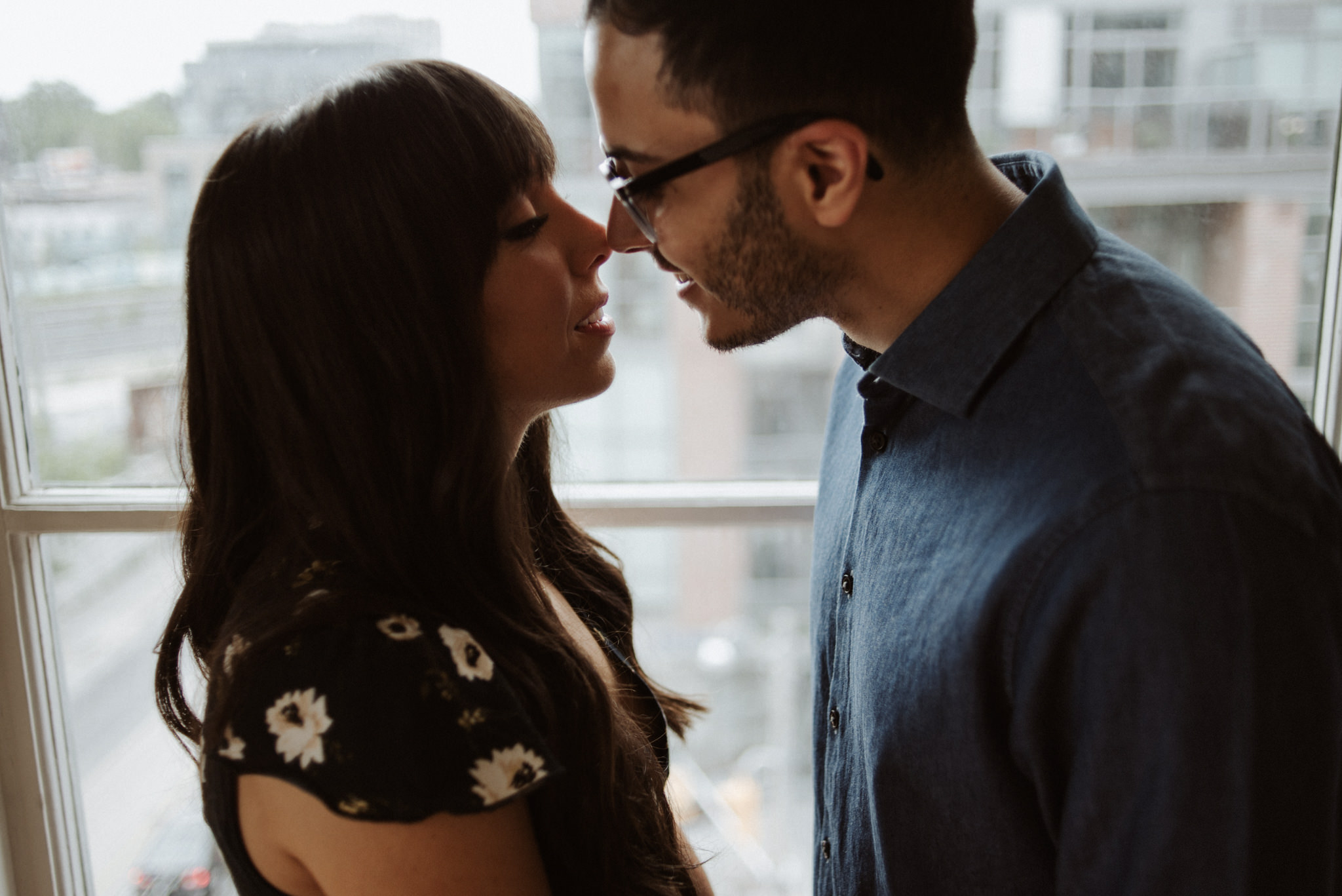 couple about to kiss in front of window