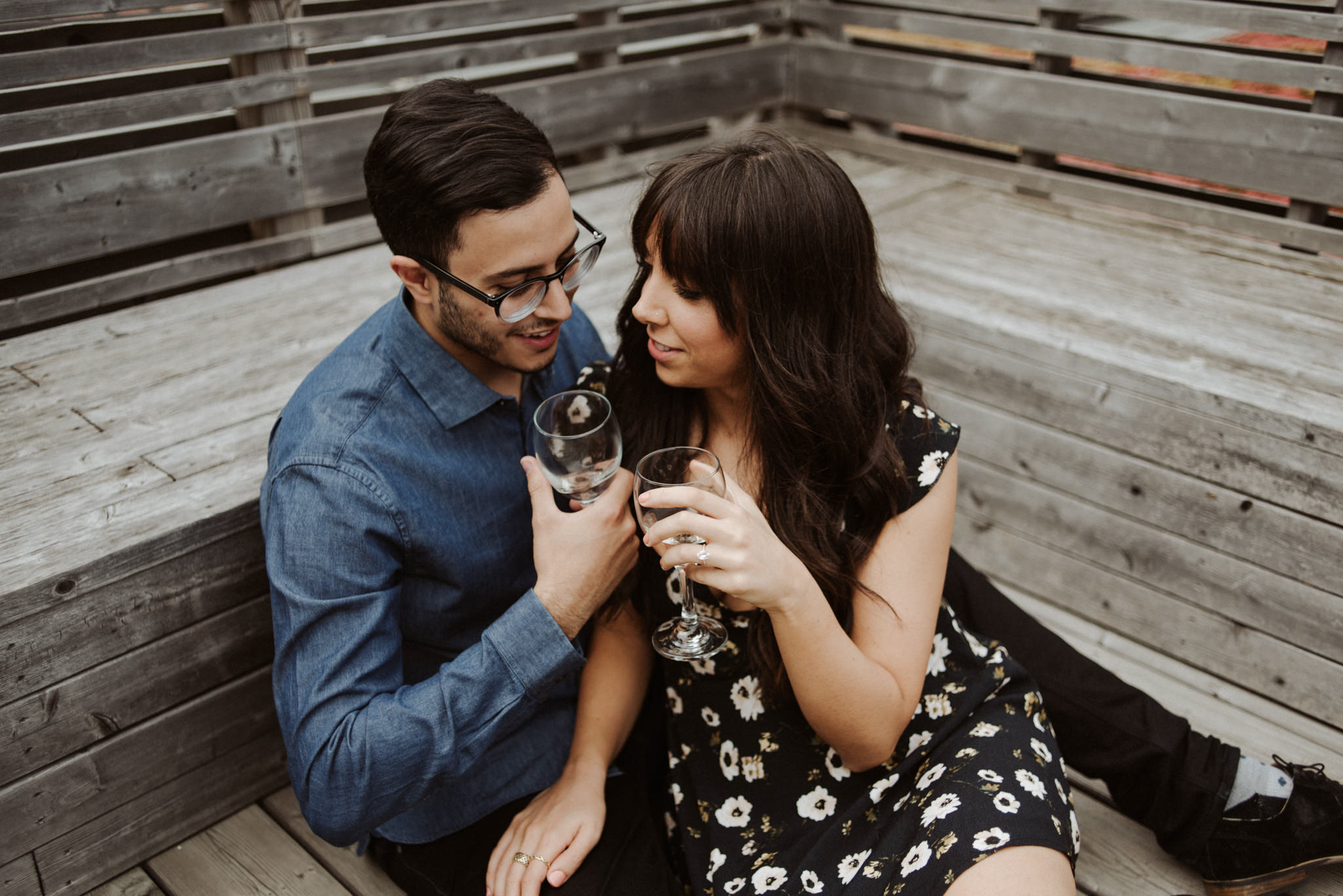 couple cuddling on rooftop and drinking wine
