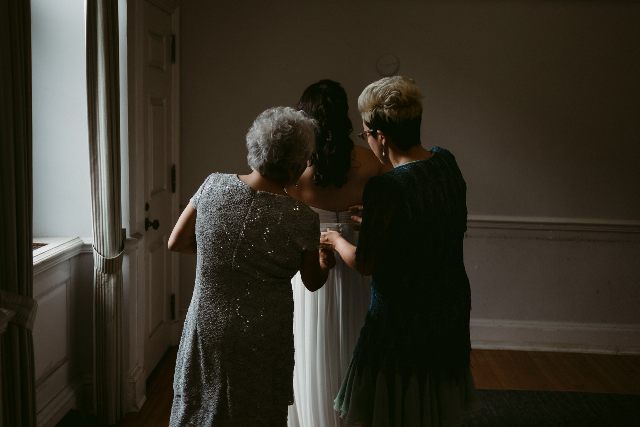 mother and sister helping bride get ready