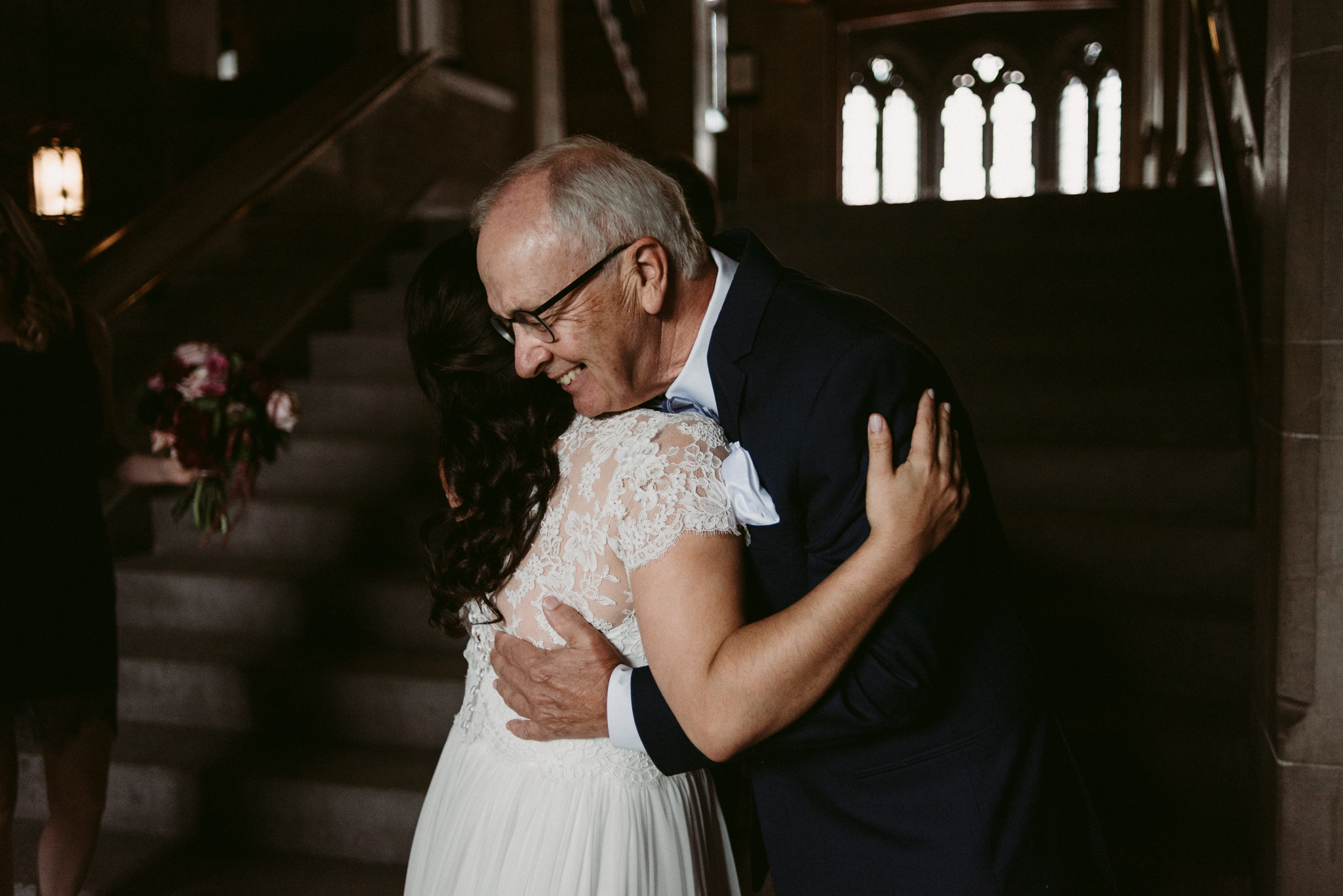 father of bride hugging bride