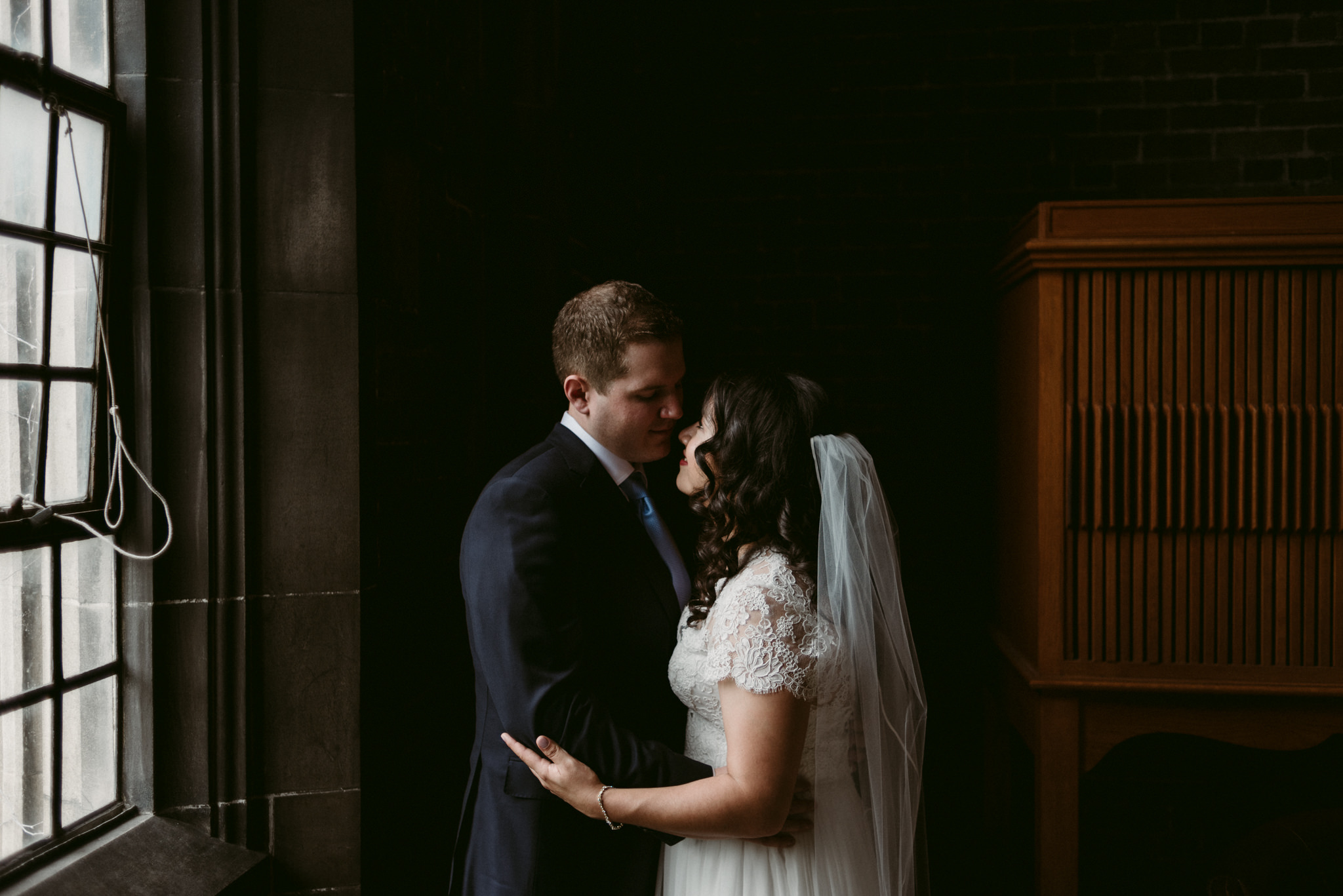 couple on wedding day hugging and looking at each other inside Hart House