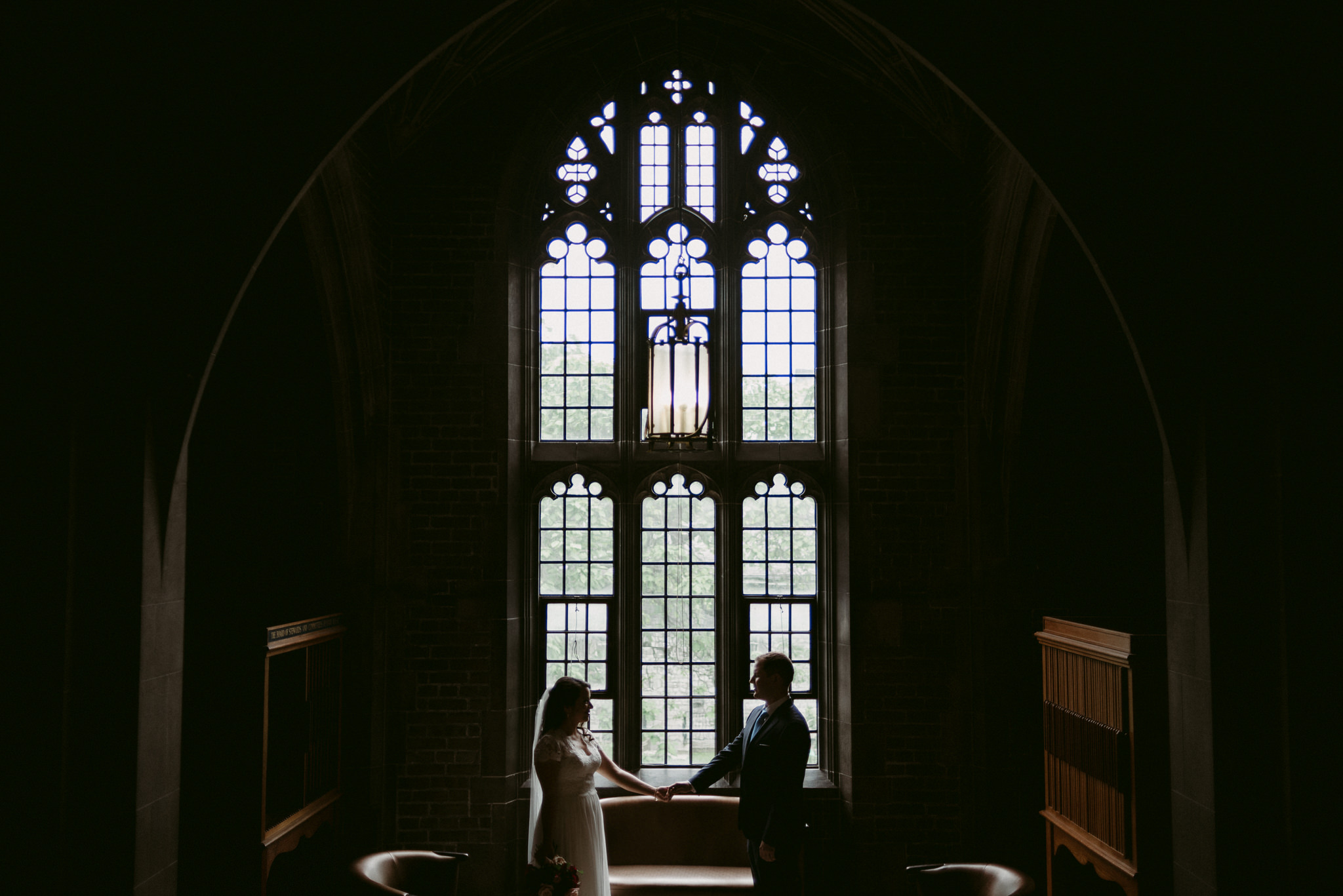 Couple holding hands in front of large windows in Hart House
