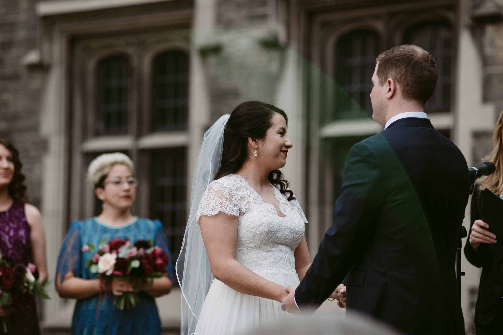 Bride and groom holding hands during wedding ceremony at Hart House