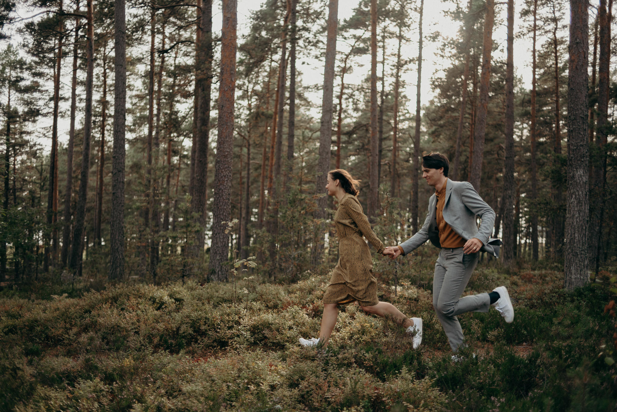 couple holding hands and running in forest