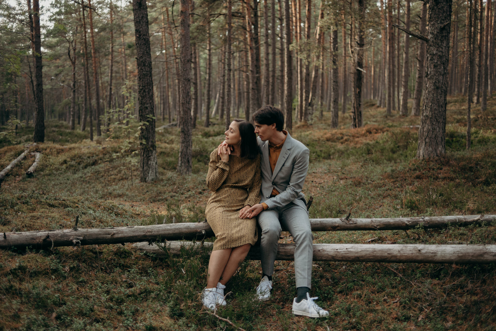 young couple sitting on fallen tree in forest