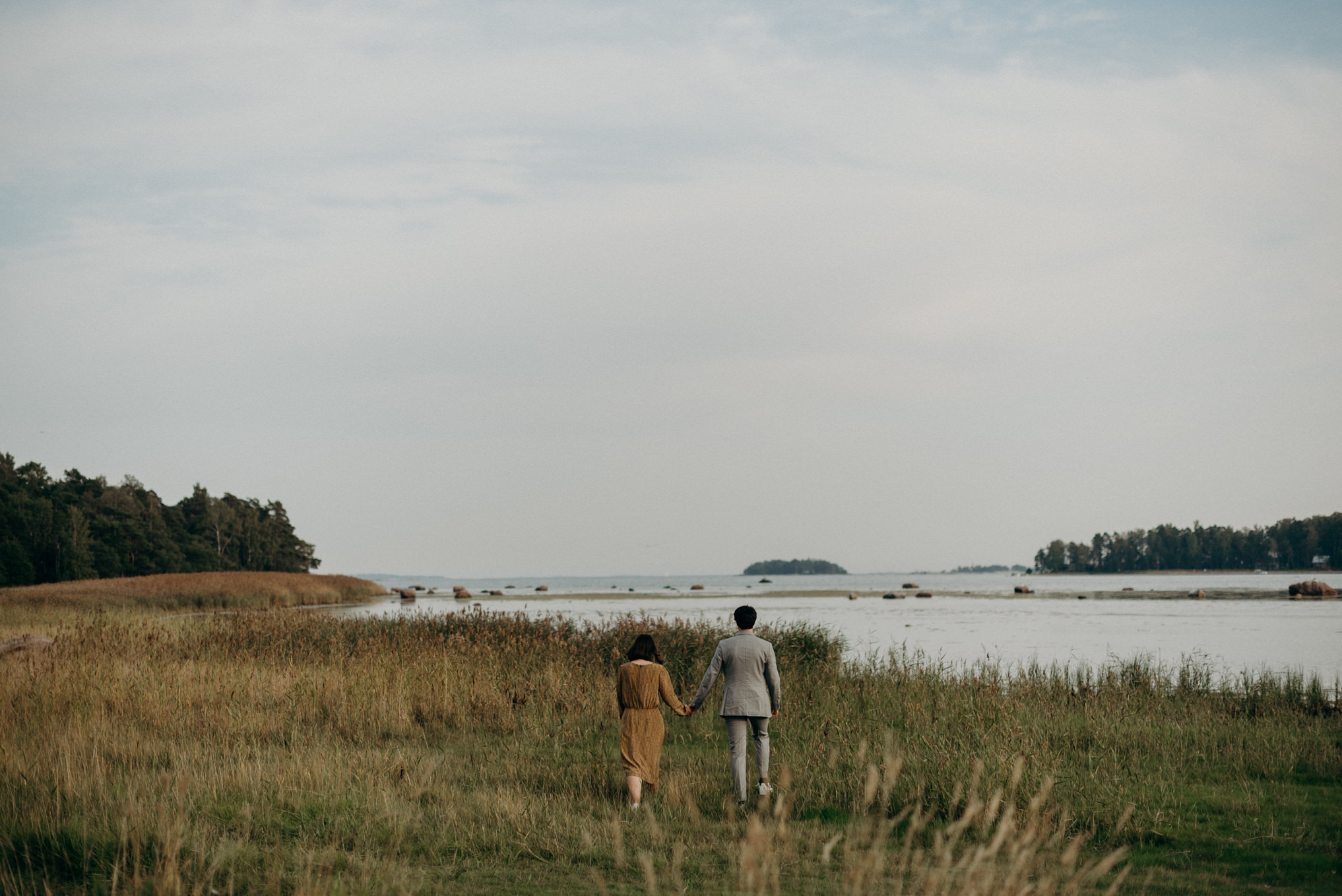 couple walking in grass towards water
