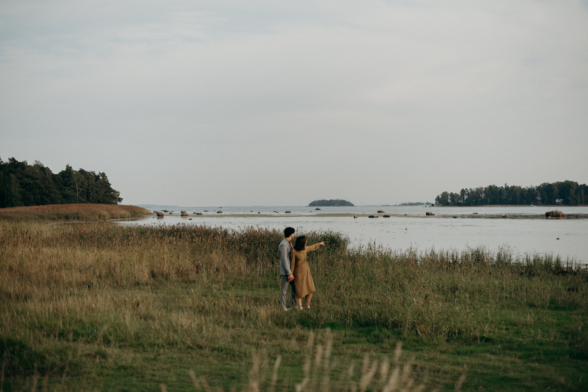 couple dressed up and standing by the water in Finland
