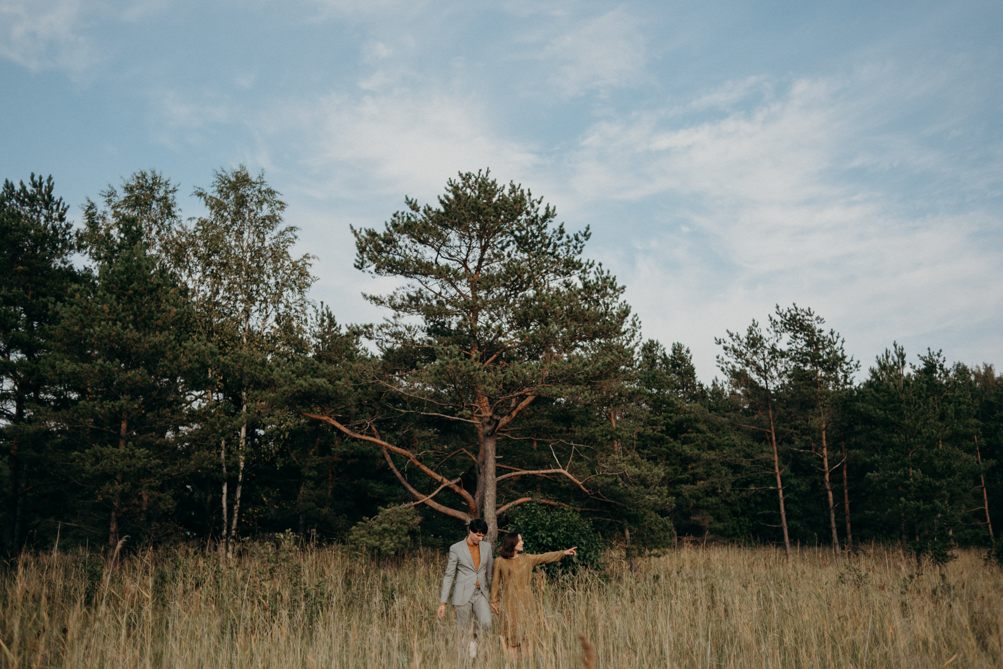 man in suit and woman in dress walking in tall grass near forest in Helsinki