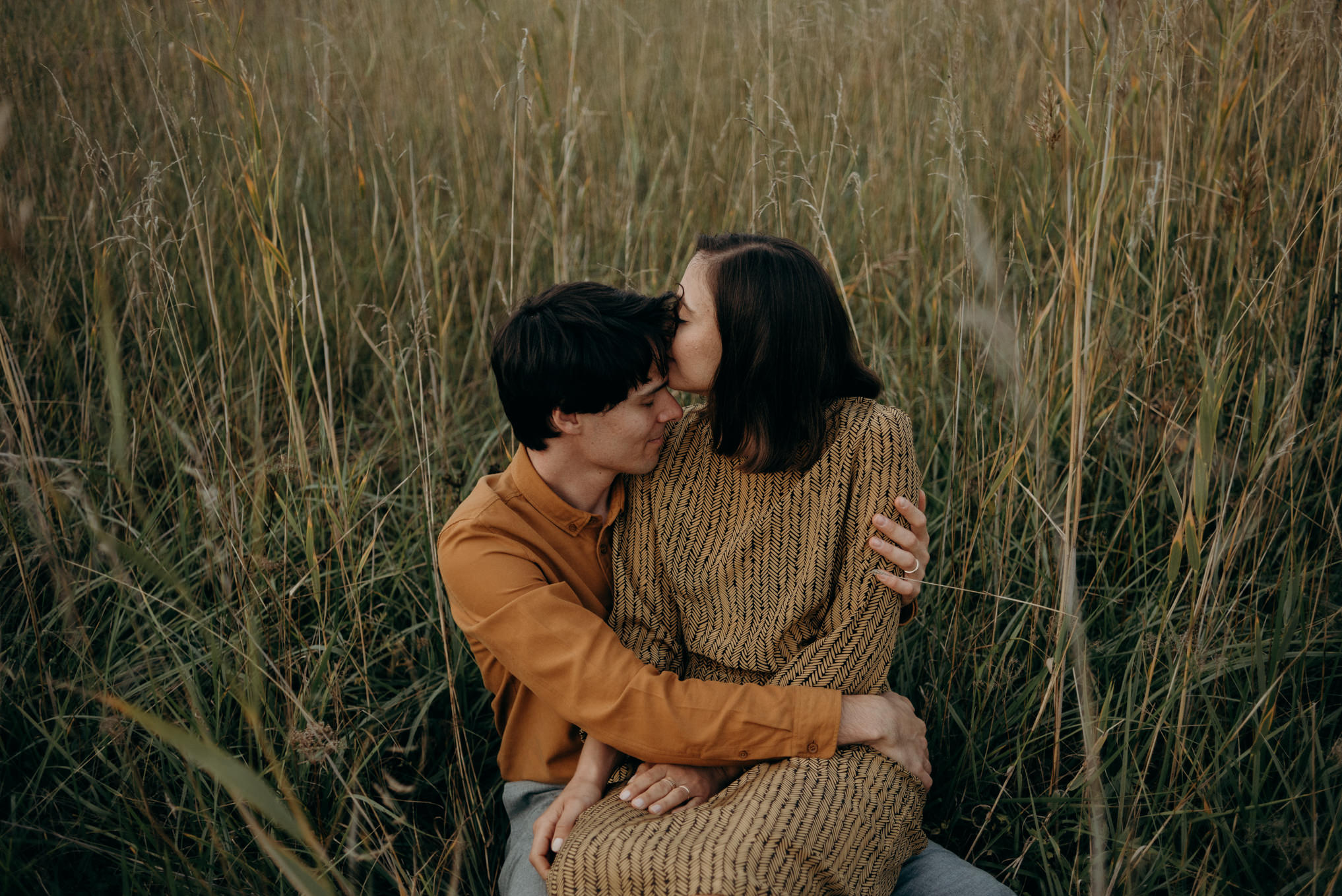 couple in love sitting in tall grass