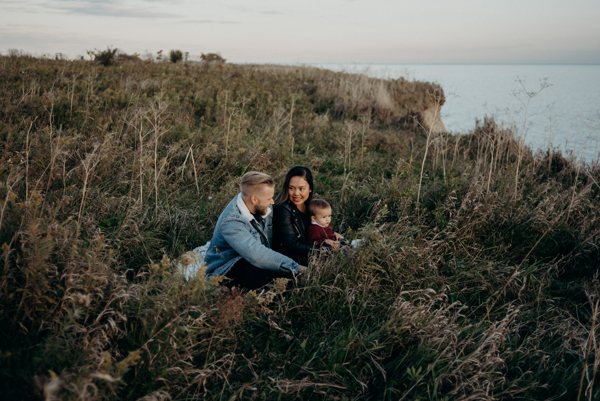 young hip couple sitting in grass by lake at sunset