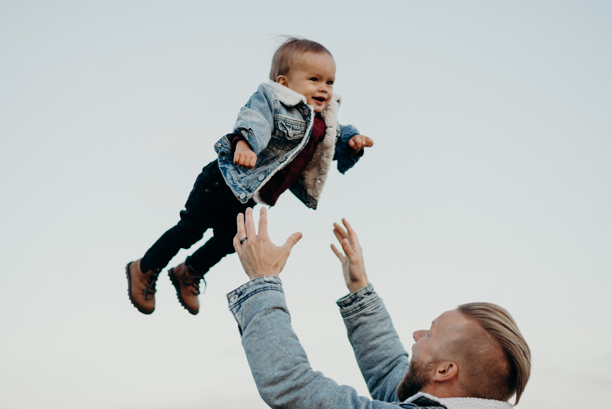 dad throwing baby boy in air with matching jean jacket