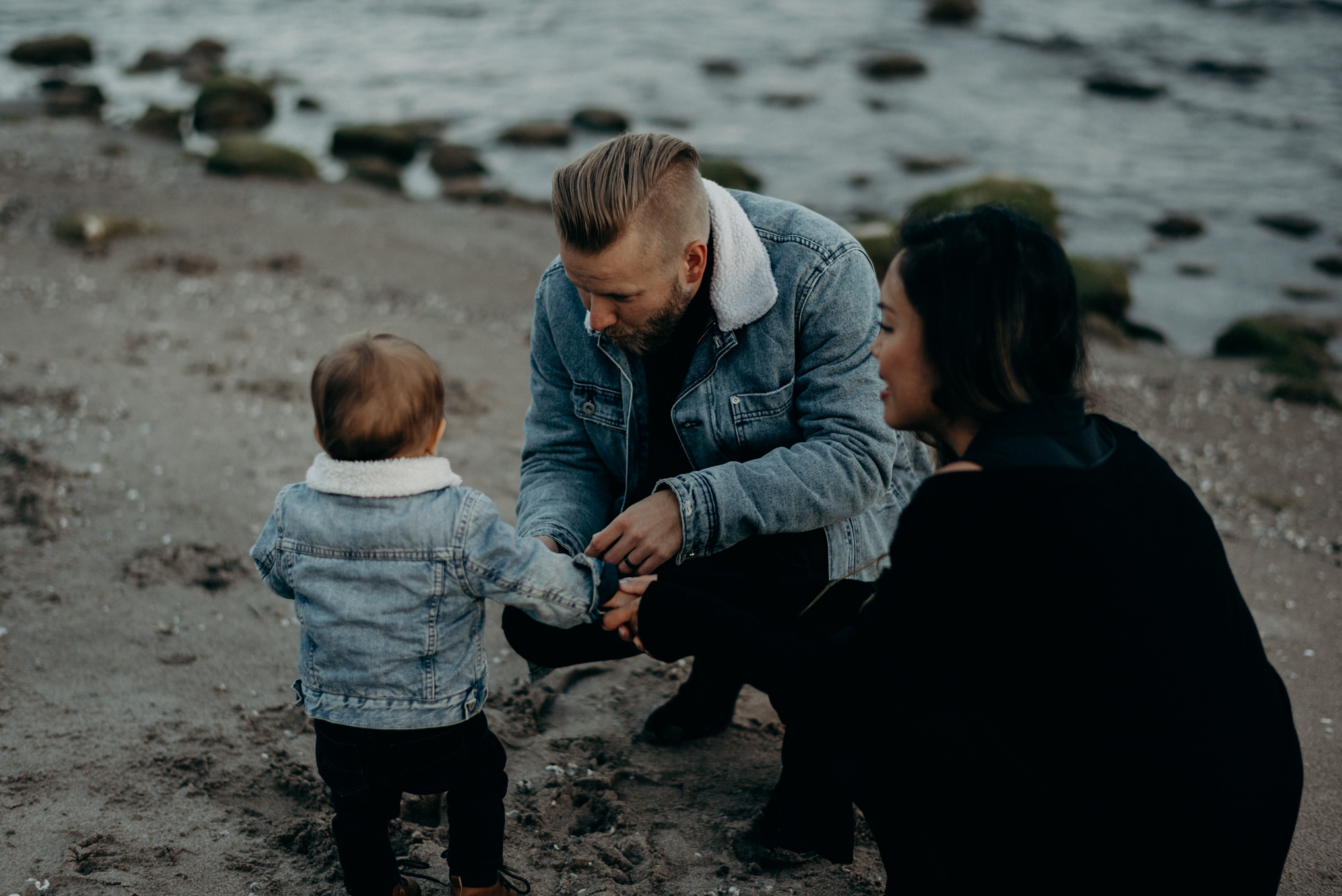 young hip couple holding baby boy on the beach