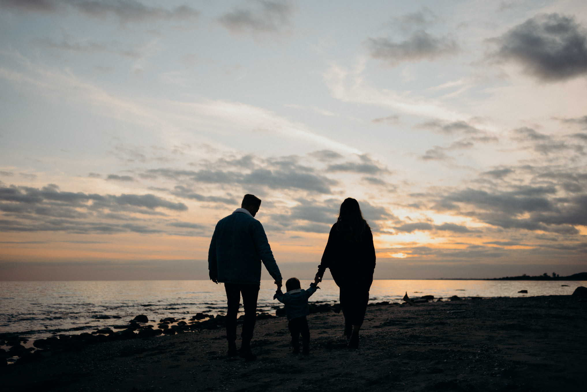 Portrait of young family watching sunset on the beach in Toronto