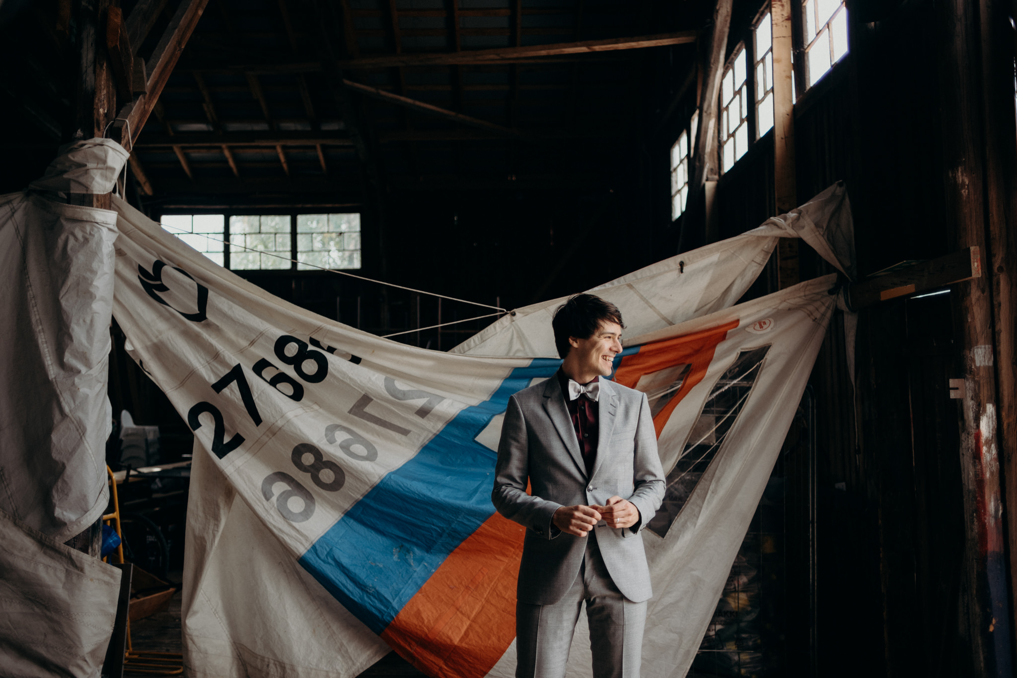 Groom standing in front of old sails in a boathouse Valkosaaren Telakka Helsinki