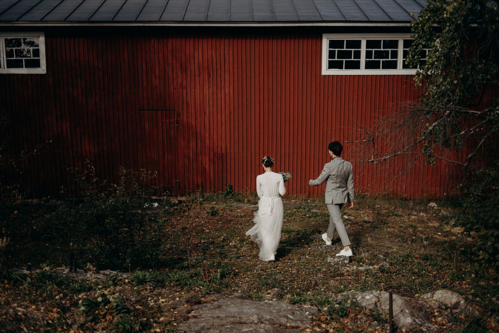 Bride and groom walking towards boathouse for portraits, Valkosaaren Telakka wedding
