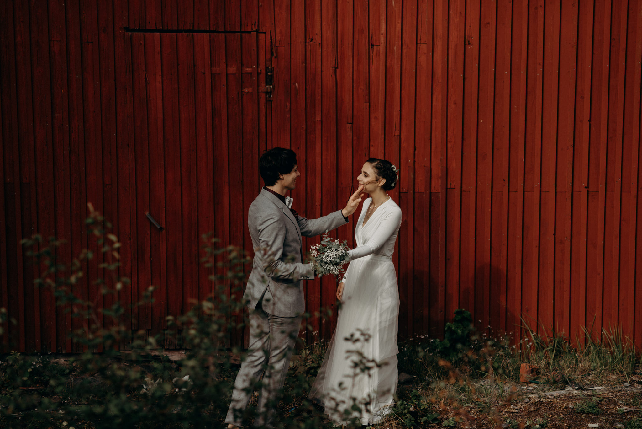 Groom removing hair from brides face in front of red barn wall