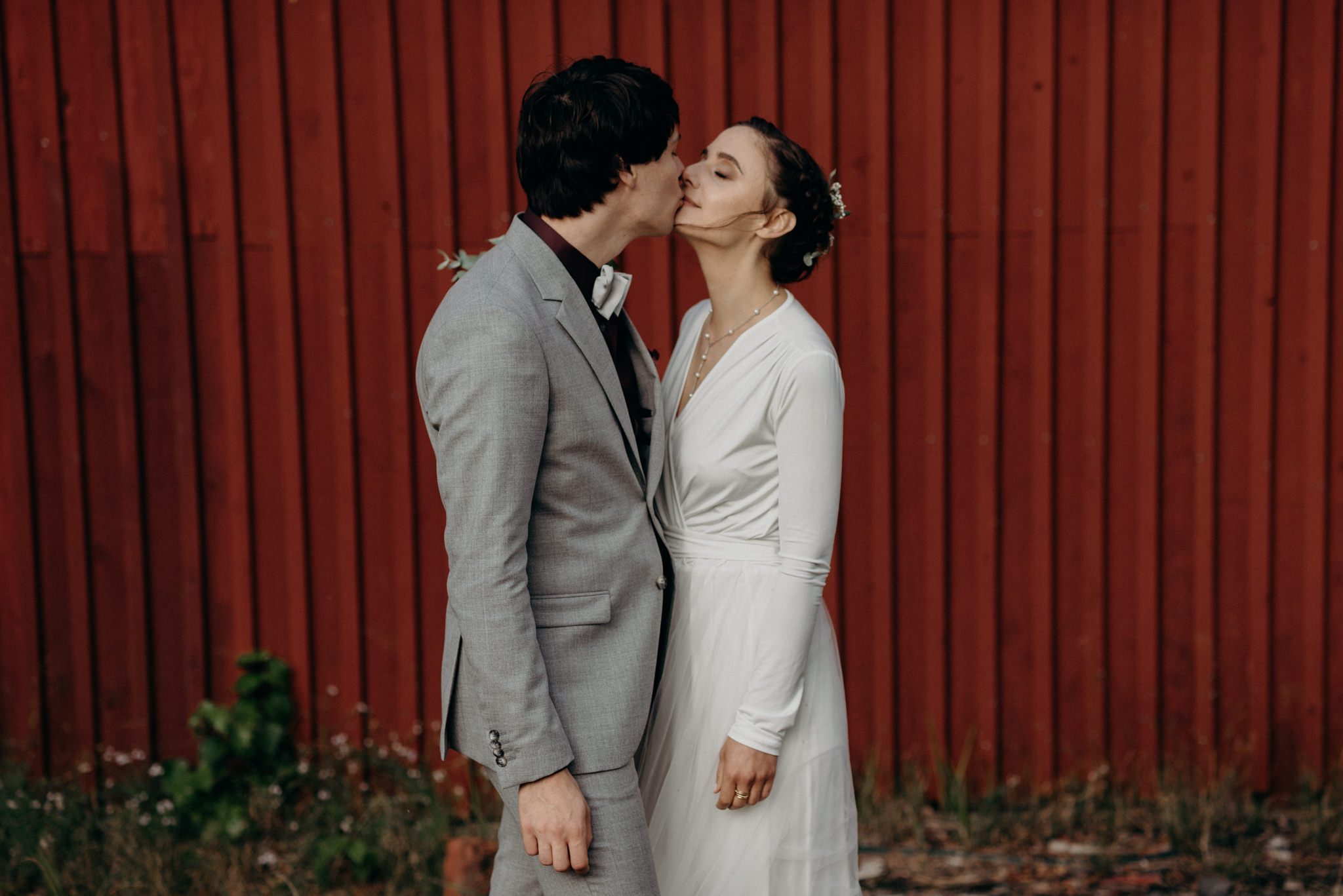 passionate kiss between bride and groom in front of red barn