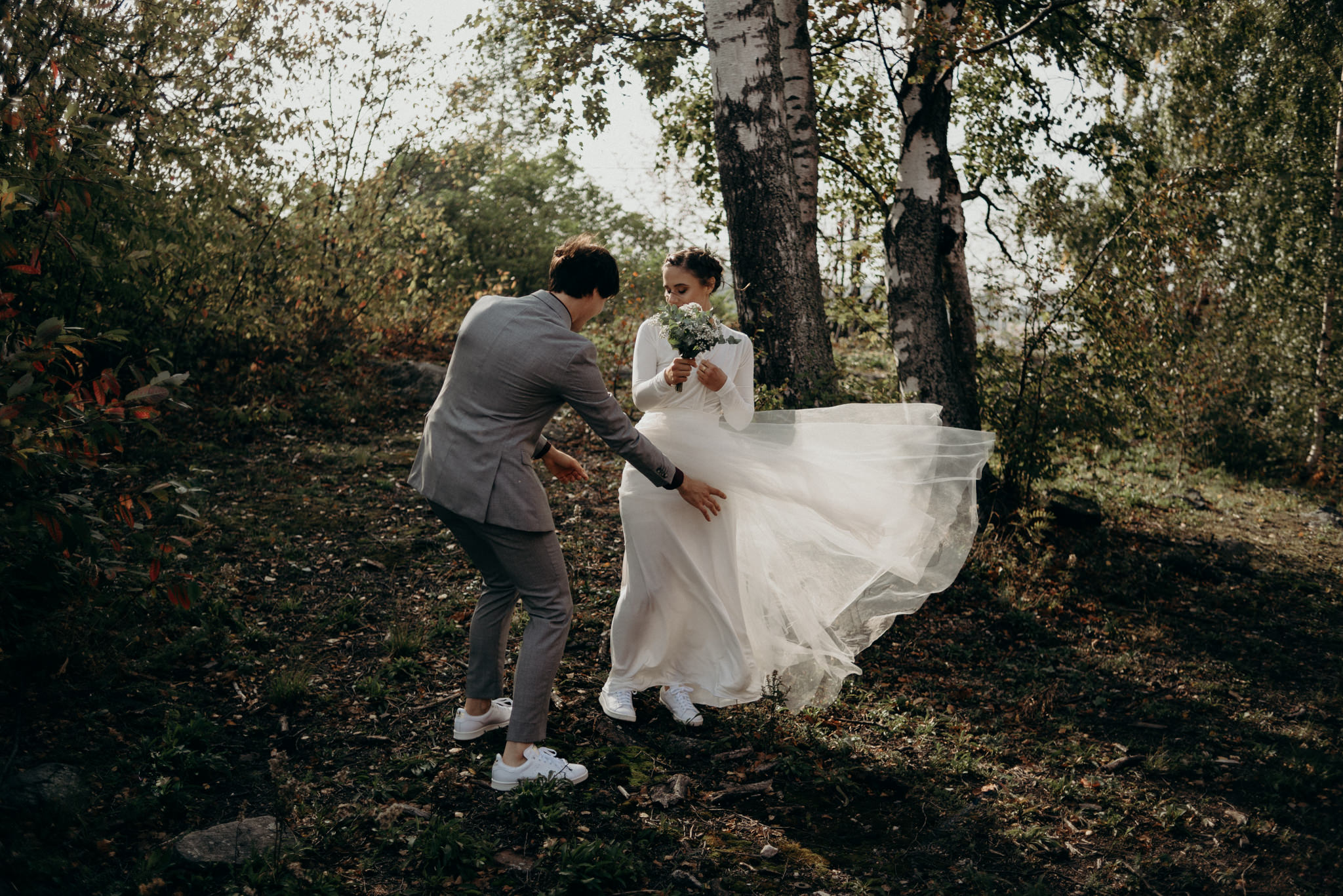 groom adjusting brides dress that is blowing in wind as they stand among trees in the sunlight