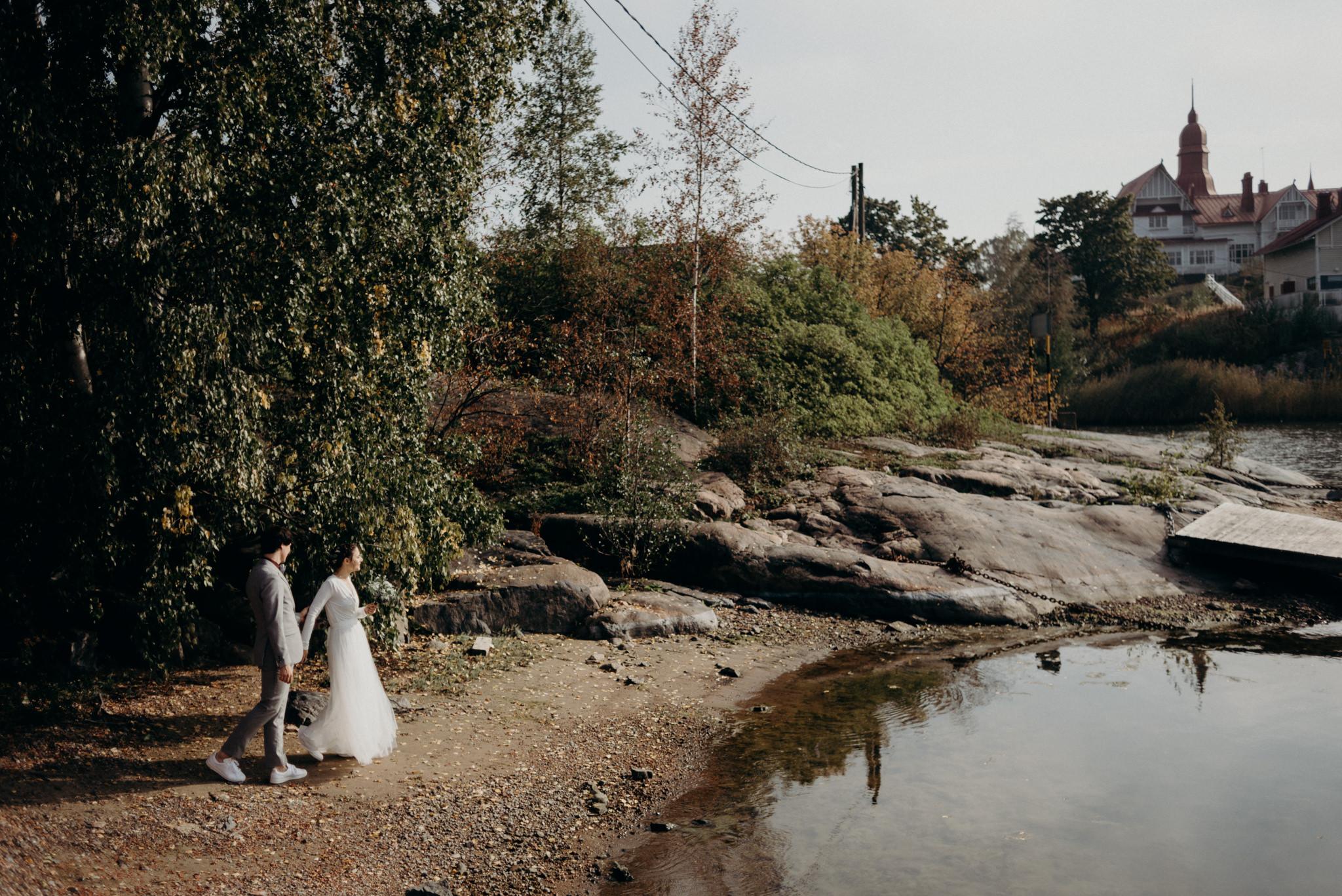 bride and groom standing by water, Helsinki wedding portraits