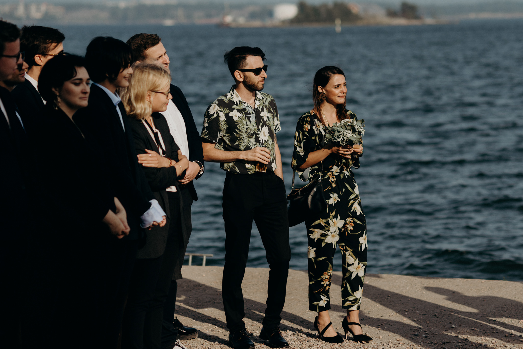 Guests cheering and clapping during outdoor wedding ceremony at Valkosaaren Telakka