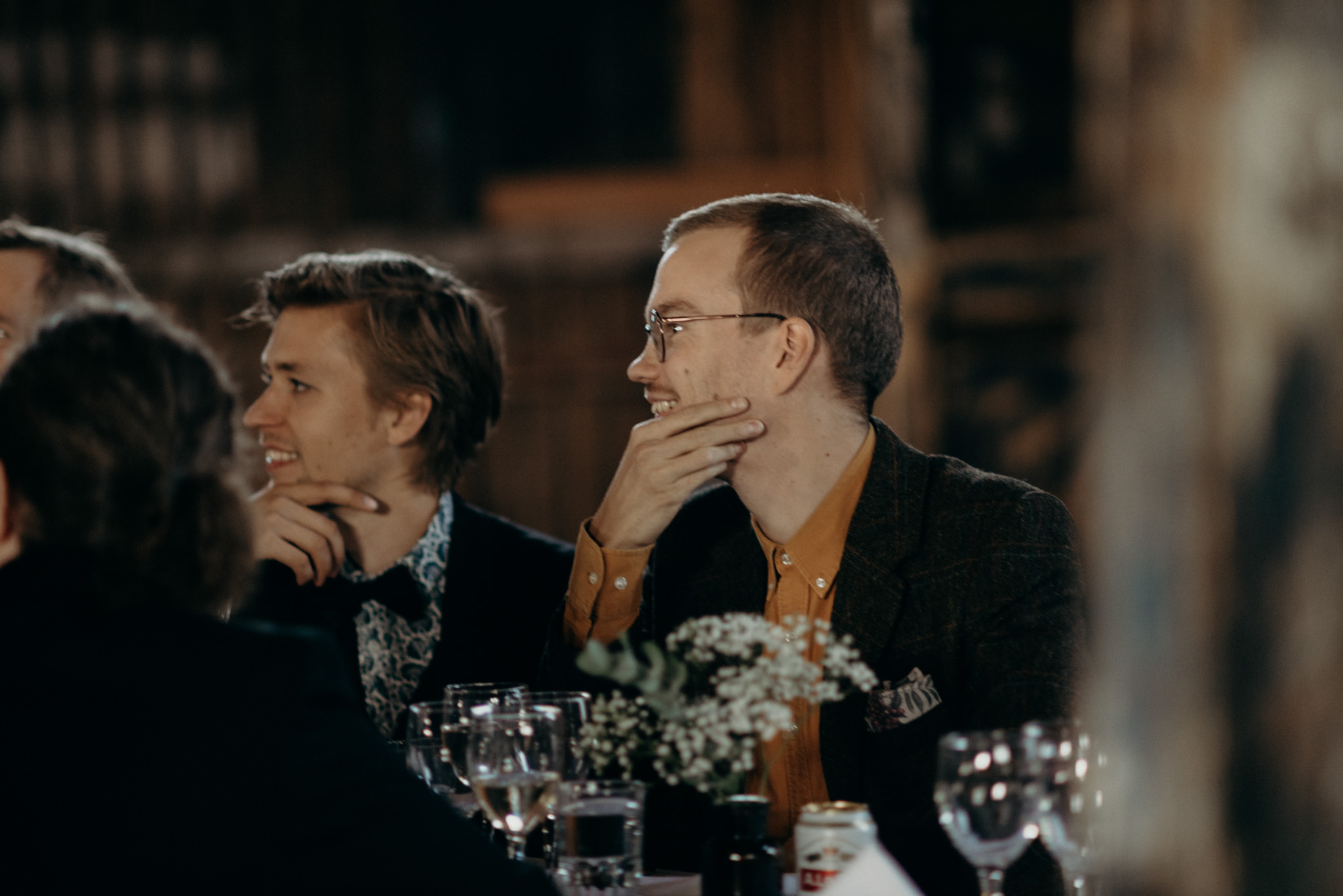 Guests listening and smiling during speeches at Valkosaaren Telakka wedding reception
