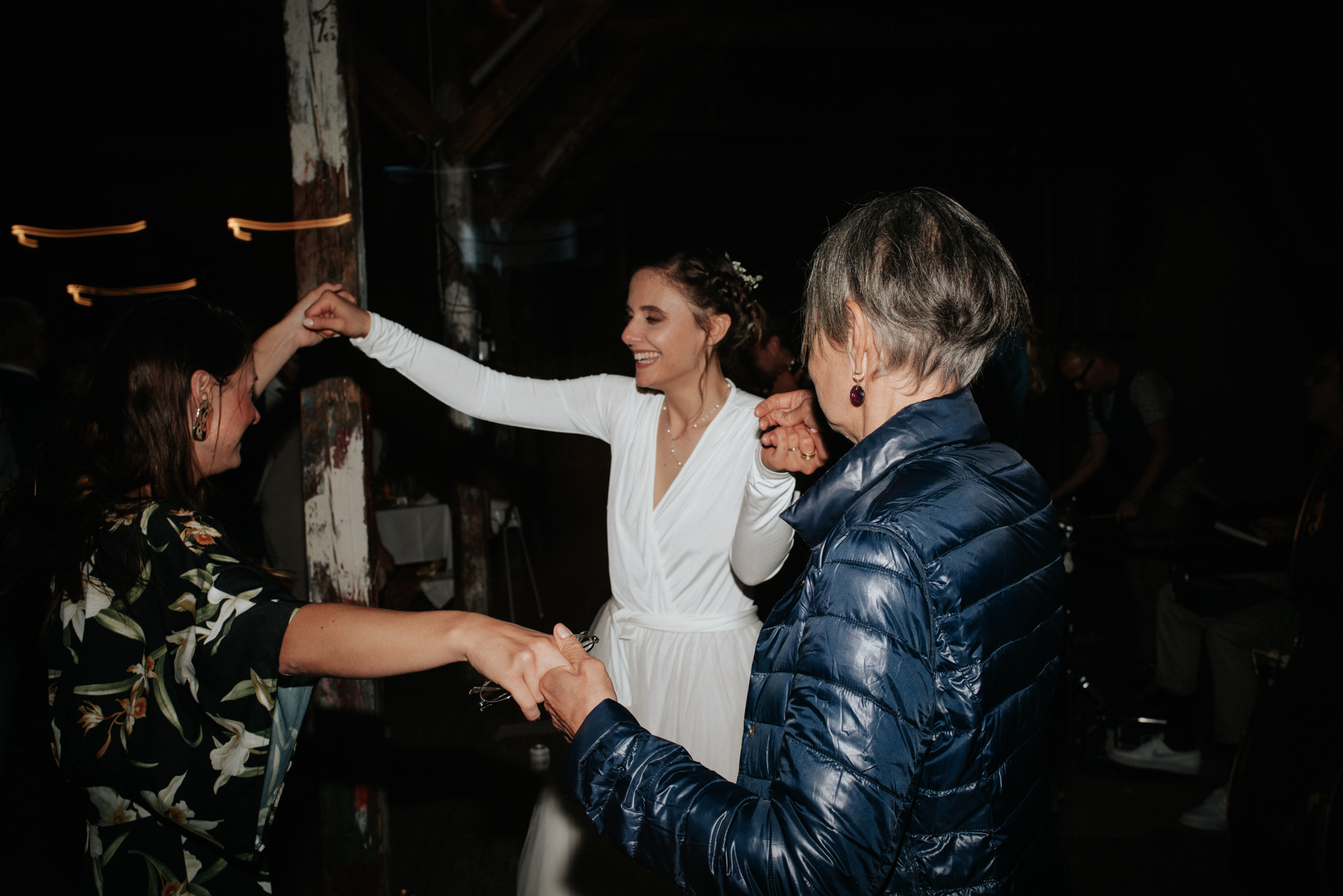 bride dancing with sister and mother during wedding reception