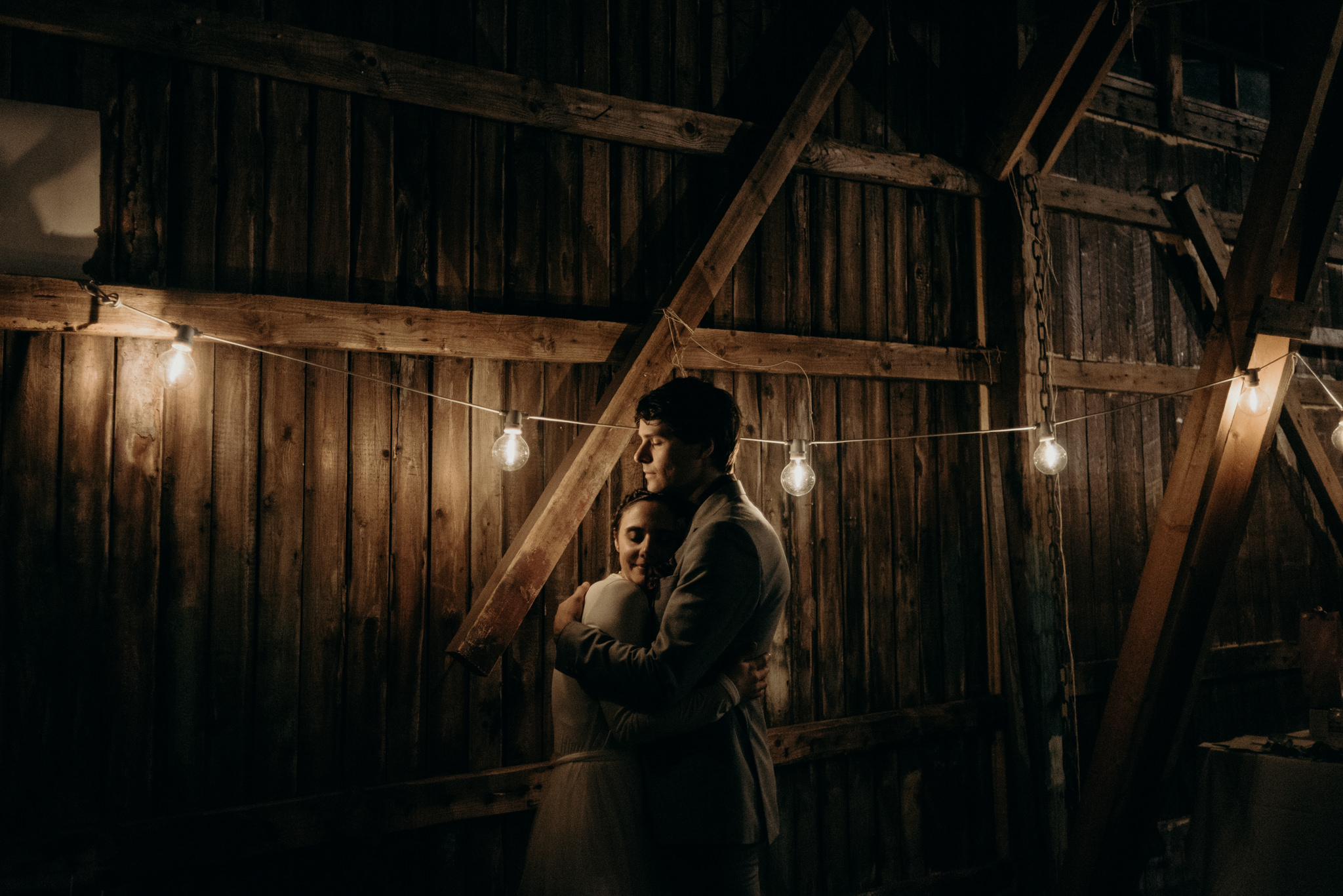 bride and groom kissing in old boathouse with stringlights at night