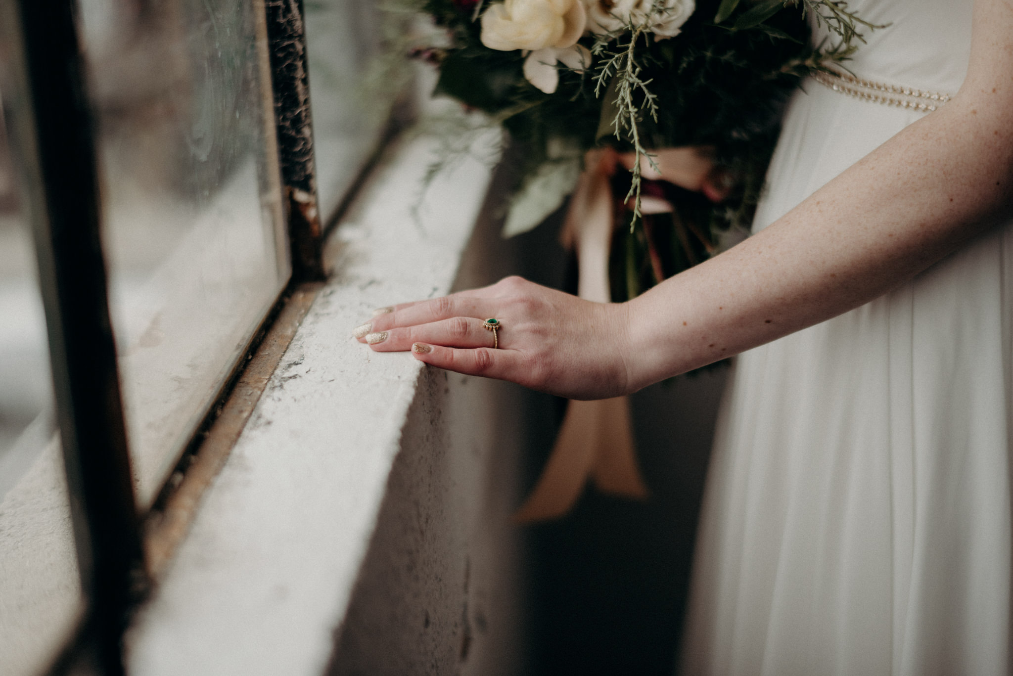 bride and groom holding hands in front of large windows of old loft in Toronto
