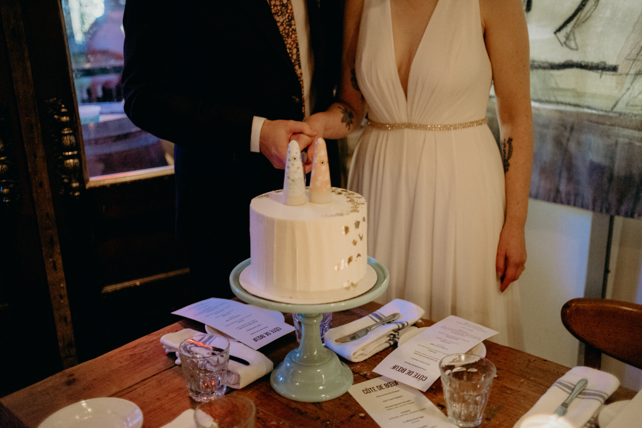 bride and groom cutting cake in restaurant, Cote de Boeuf wedding reception