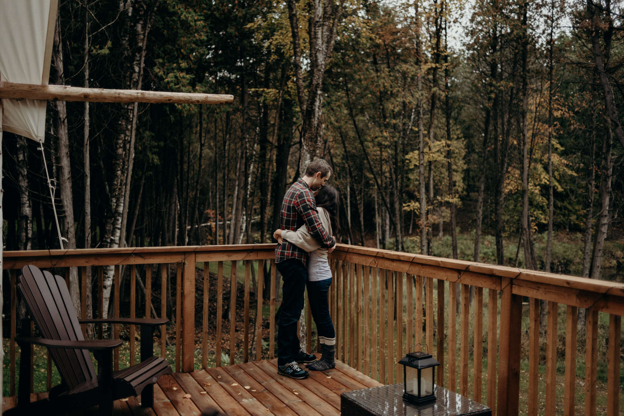 Couple hugging on deck surrounded by trees in the fall