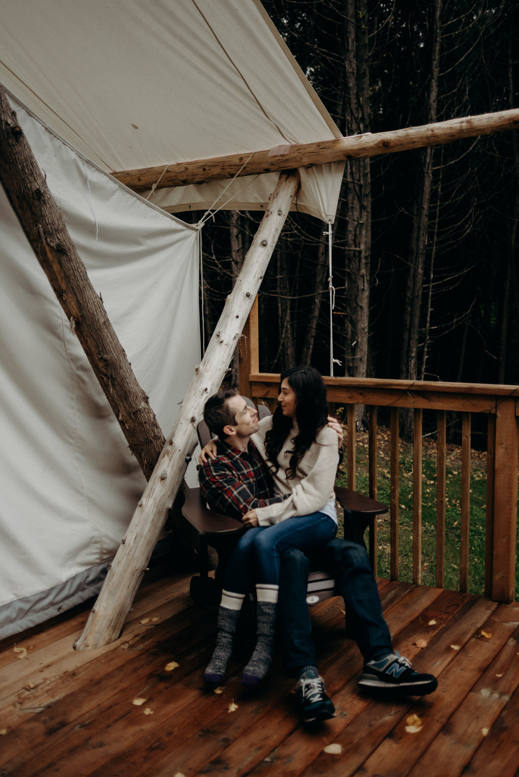 couple sitting in chair in front of glamping tent in the fall