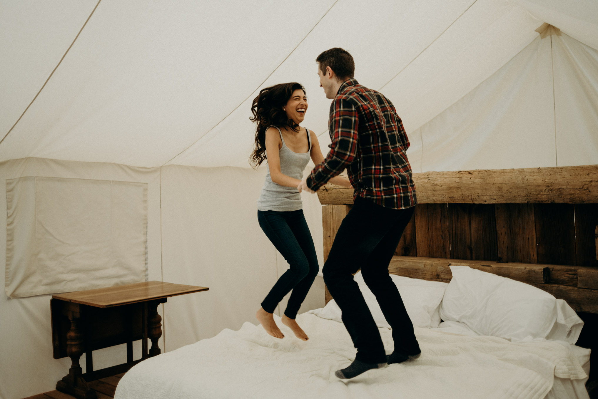 Couple jumping on bed in glamping tent at Whispering Springs