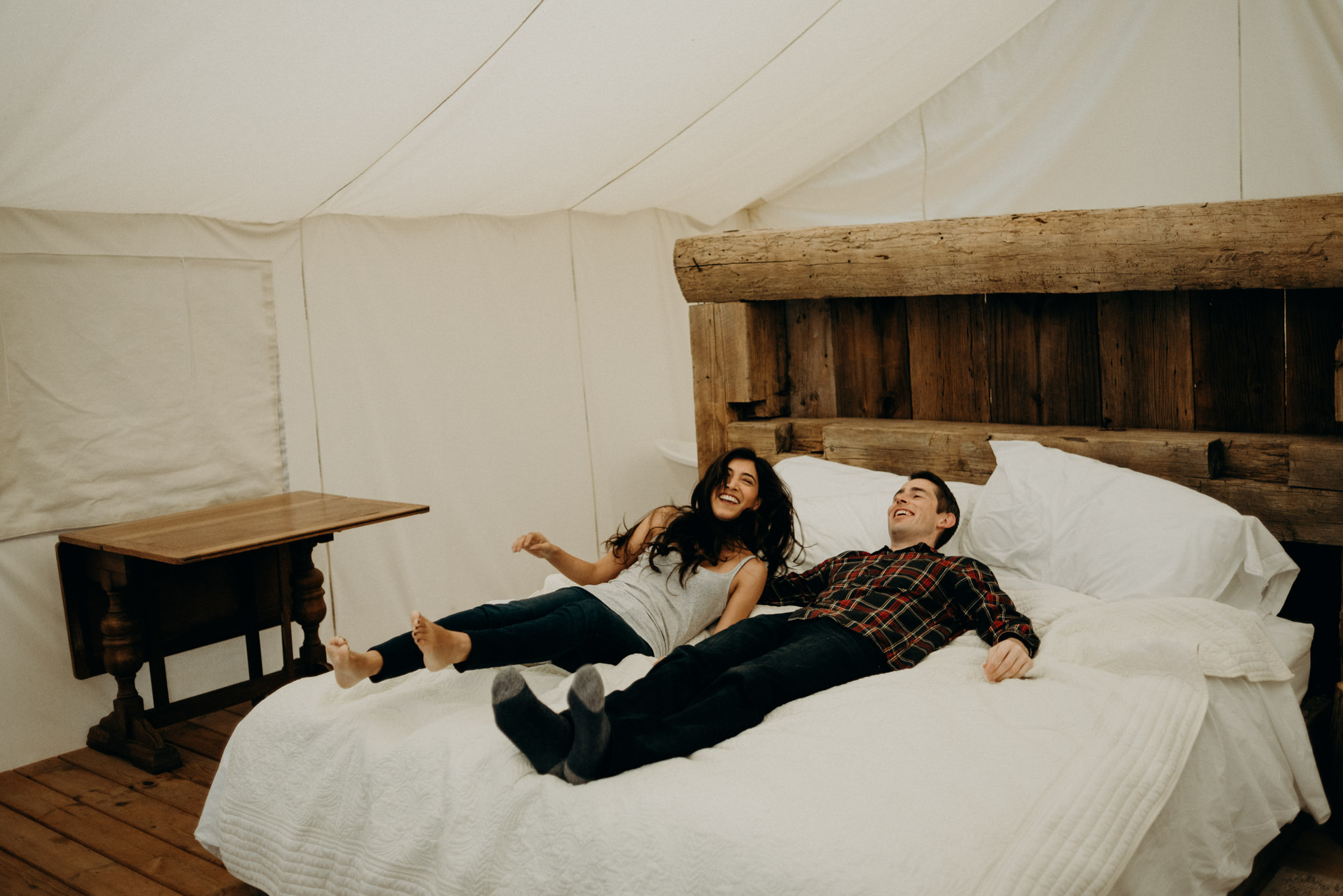 Couple lying on bed in glamping tent at Whispering Springs