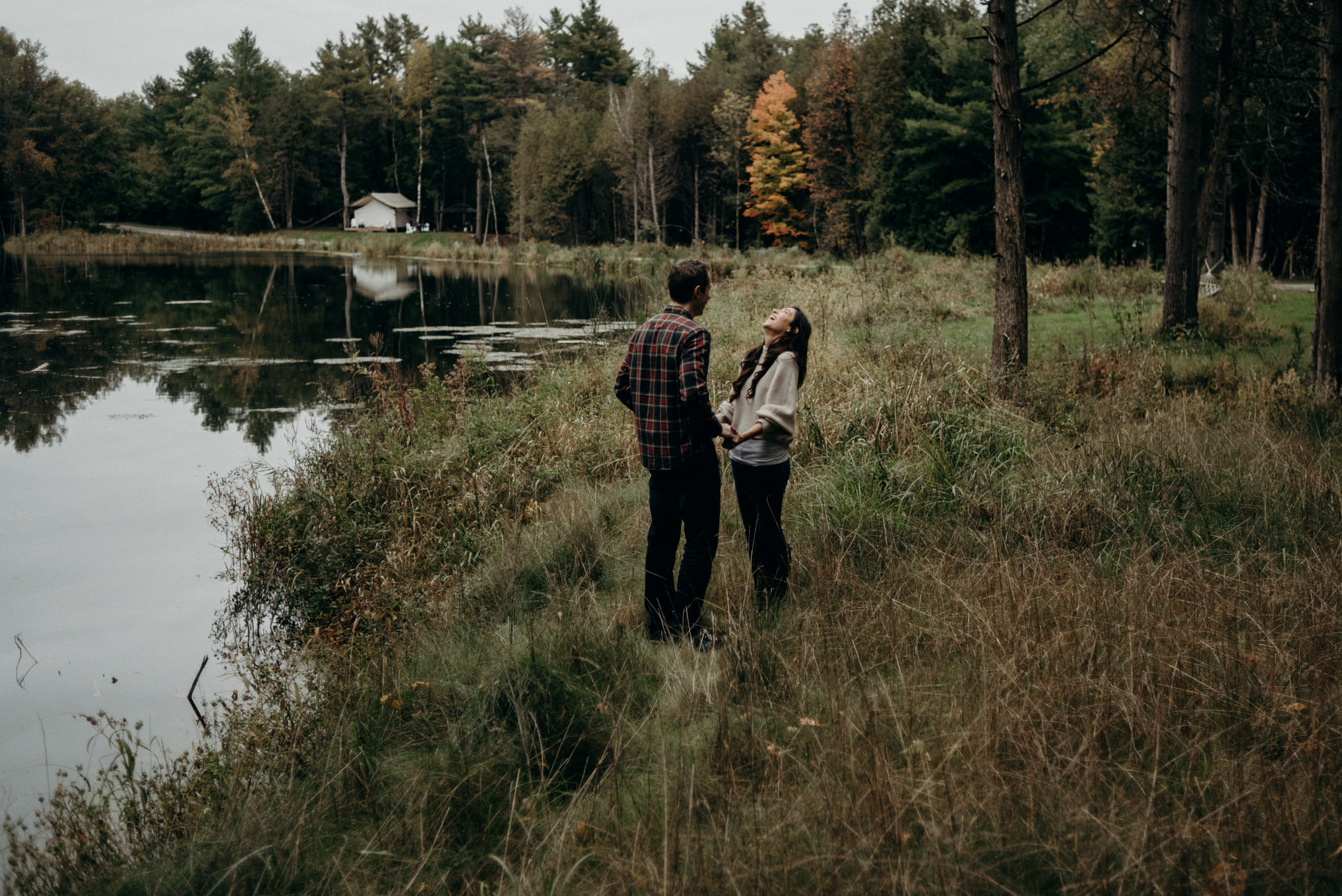 Couple laughing and hugging outside by water in the fall