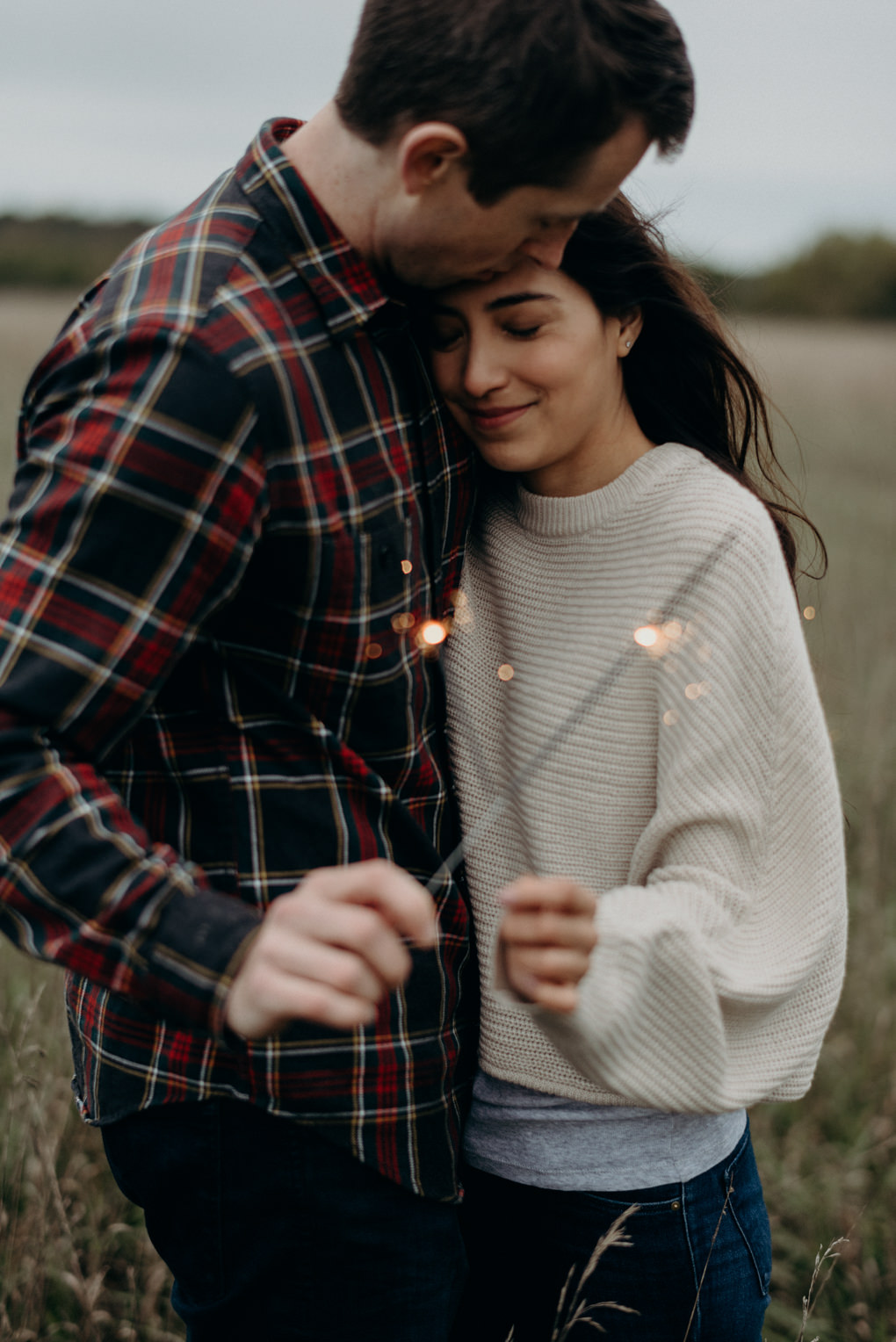 Couple laughing and holding sparklers