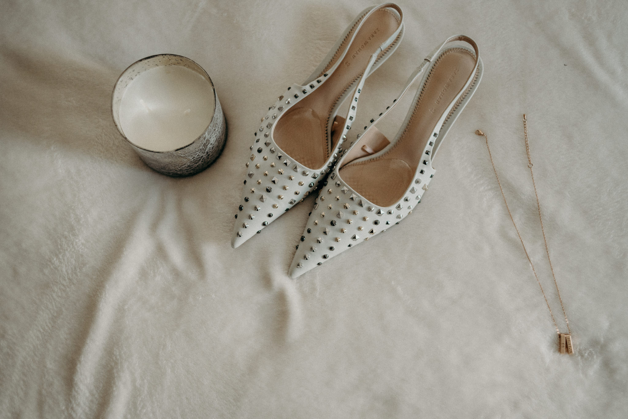 studded wedding shoes on bed