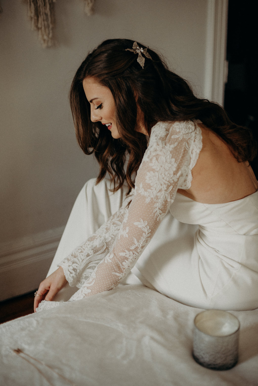 bride sitting on bed getting shoes on