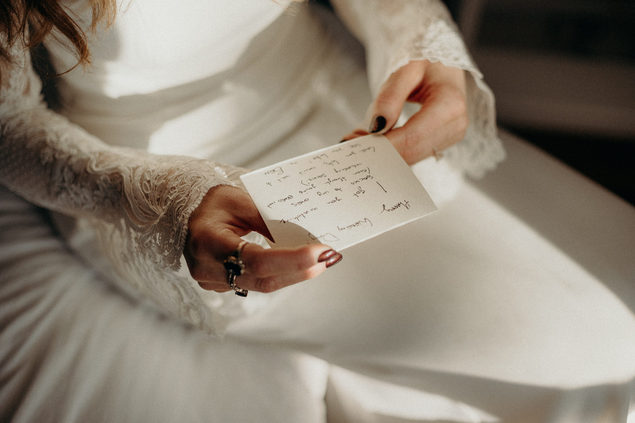 bride in wedding dress reading note from groom