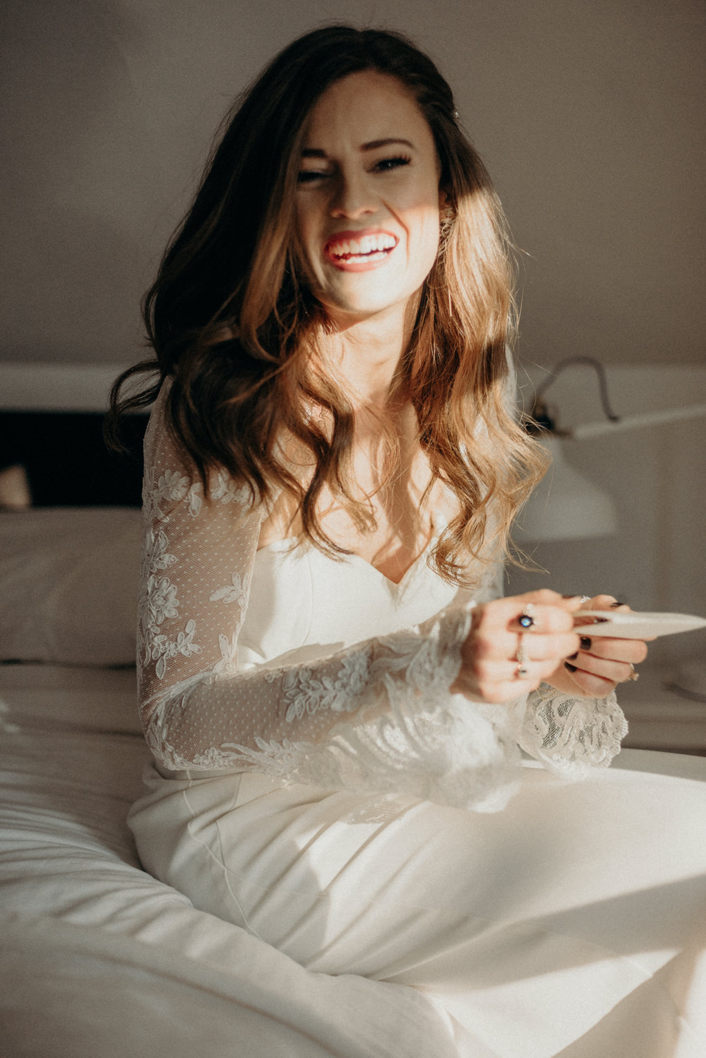 bride in wedding dress sitting on bed laughing and holding note from groom