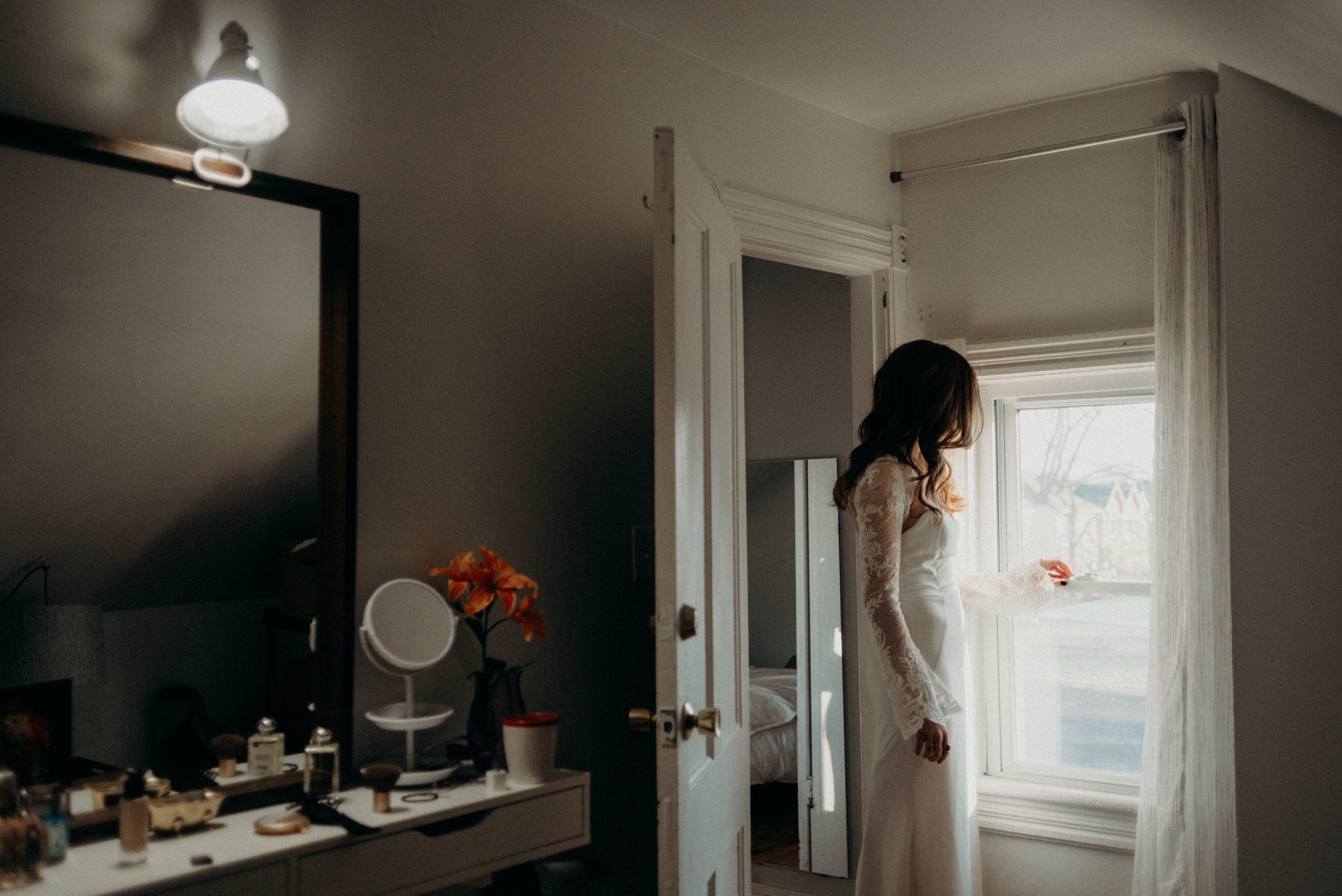 bride in wedding dress standing by window