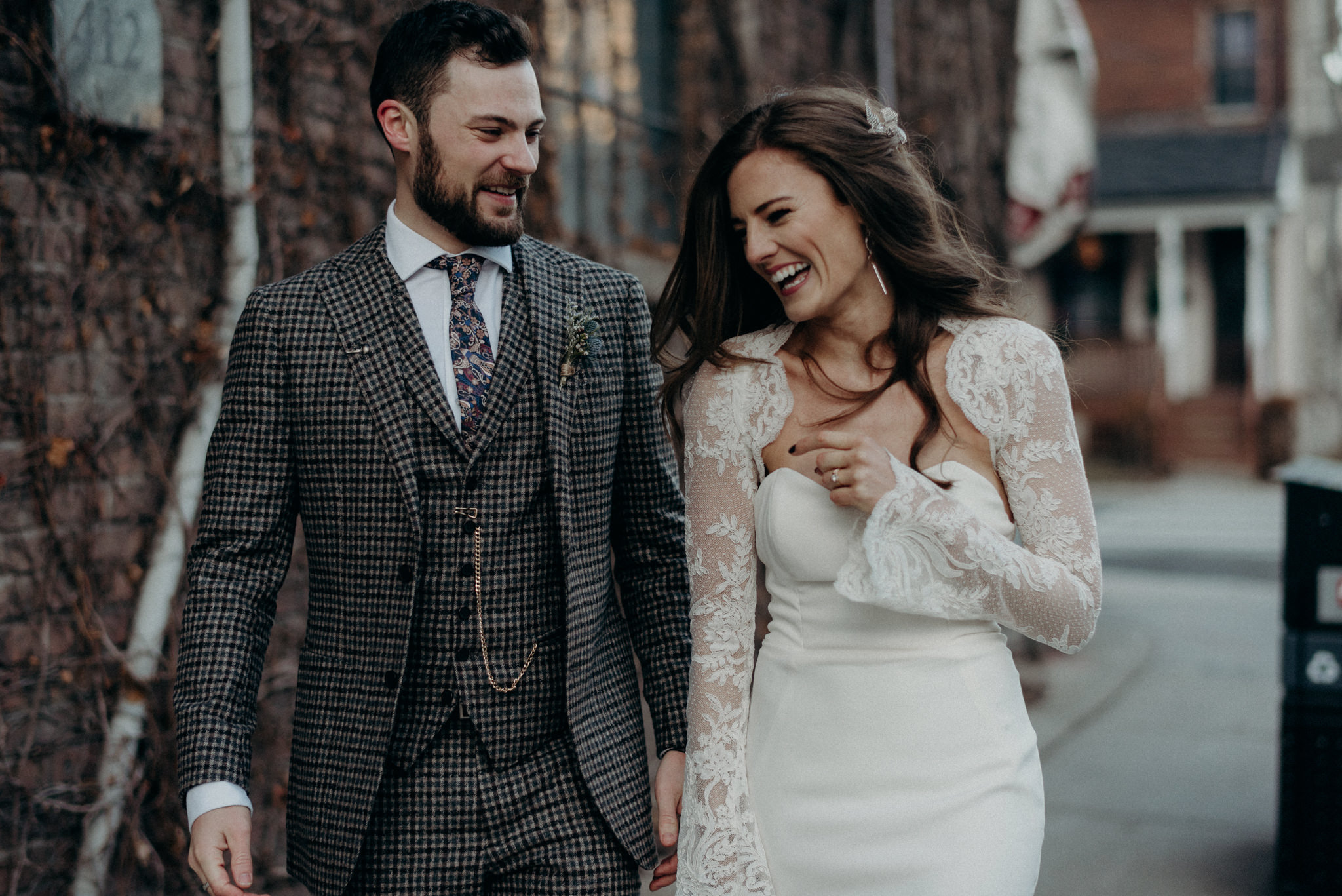 bride and groom holding hands while walking and laughing