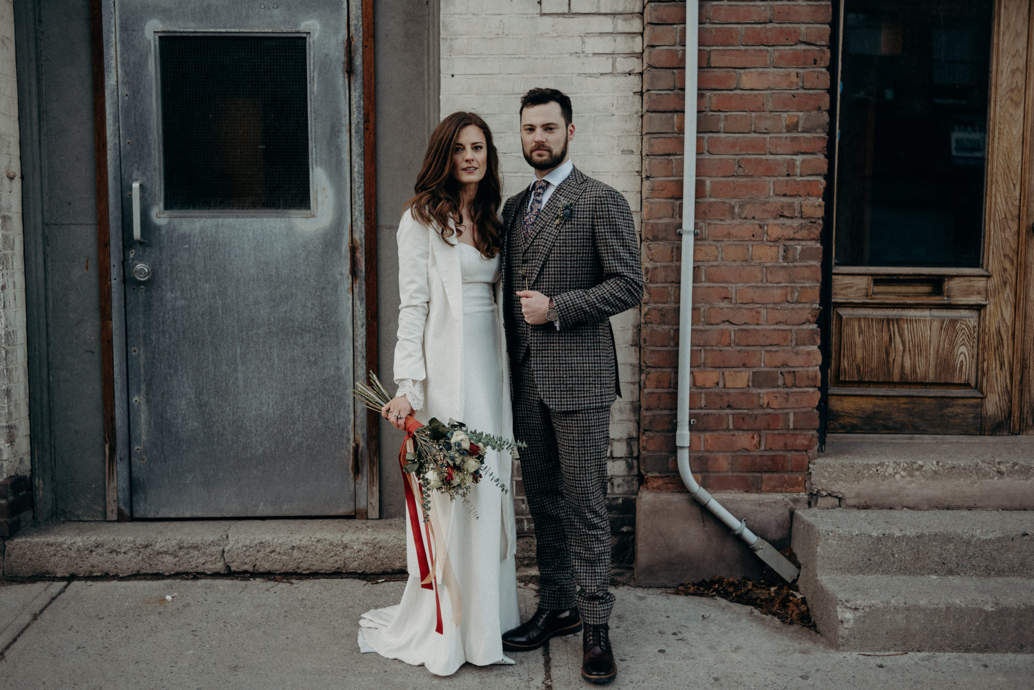 wedding portrait while standing on sidewalk in front of old building