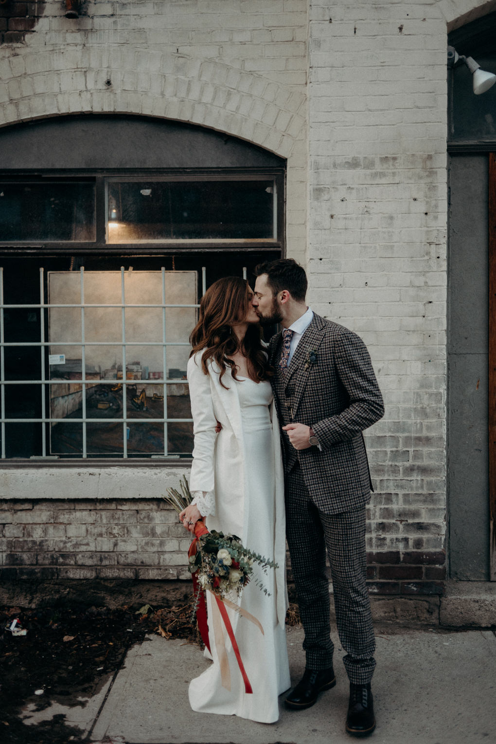 bride and groom kissing in front of old building