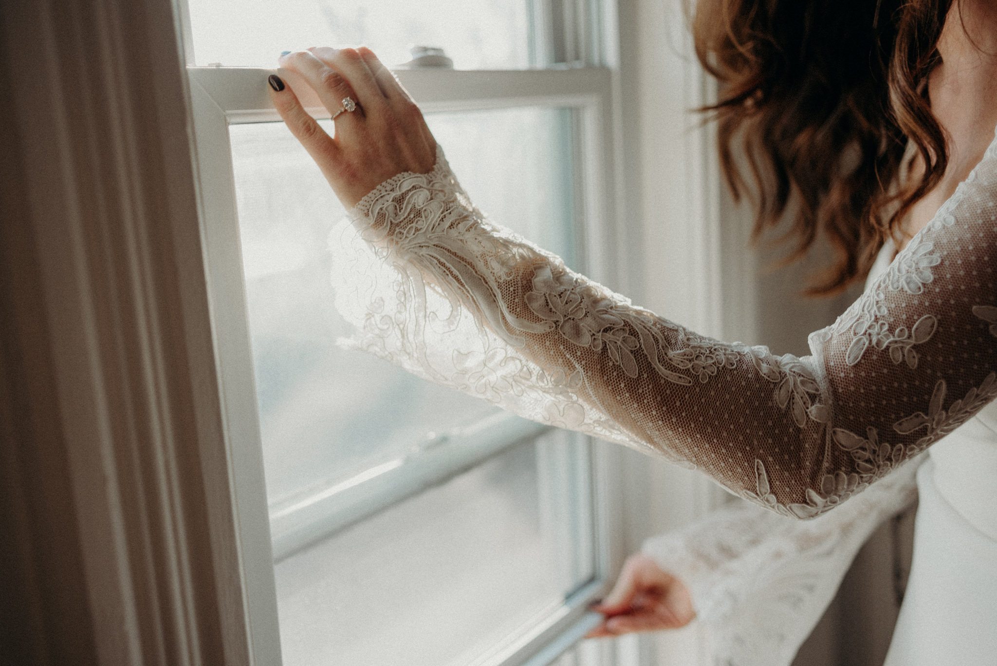 bride in long sleeve wedding dress opening window