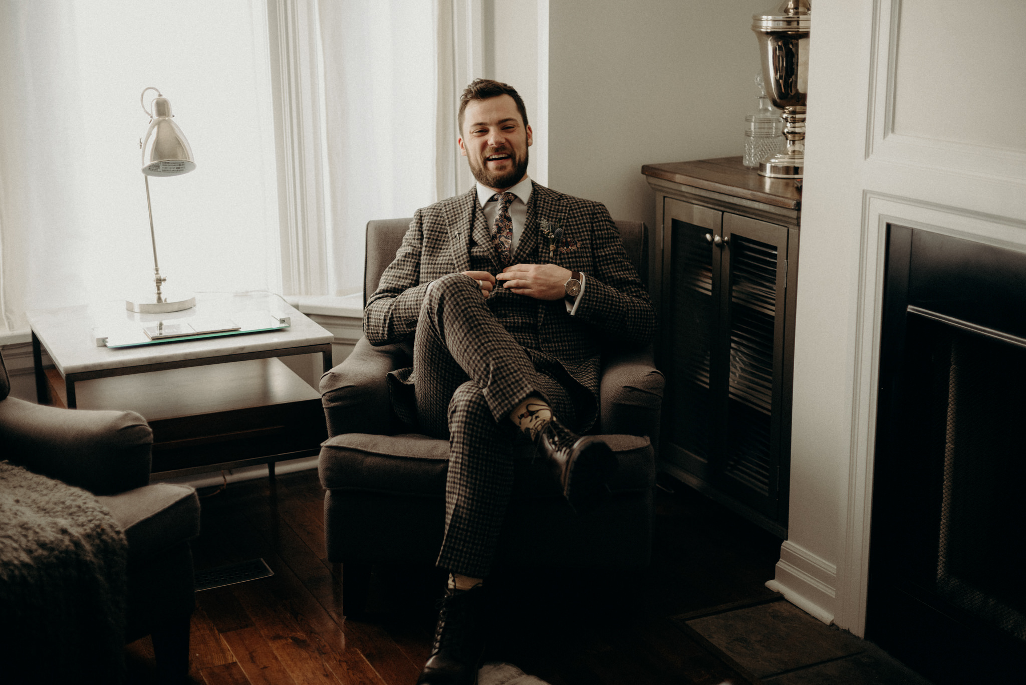 groom in wool suit sitting in chair in living room