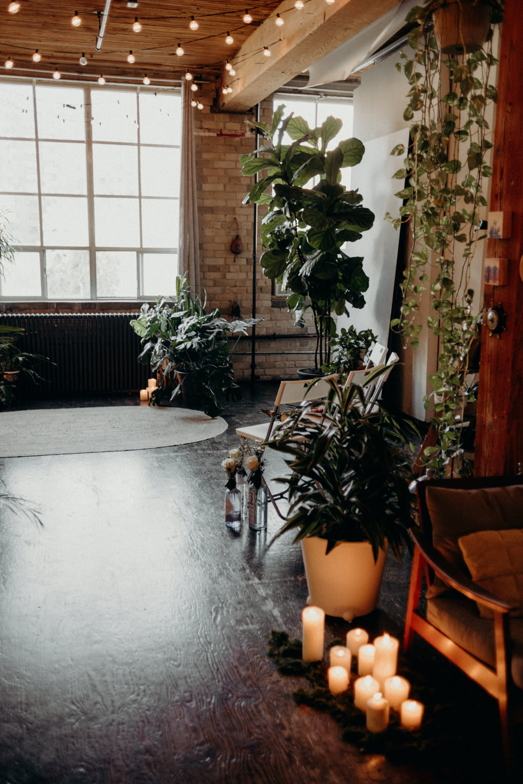 candles on the floor and lots of plants in loft for wedding ceremony