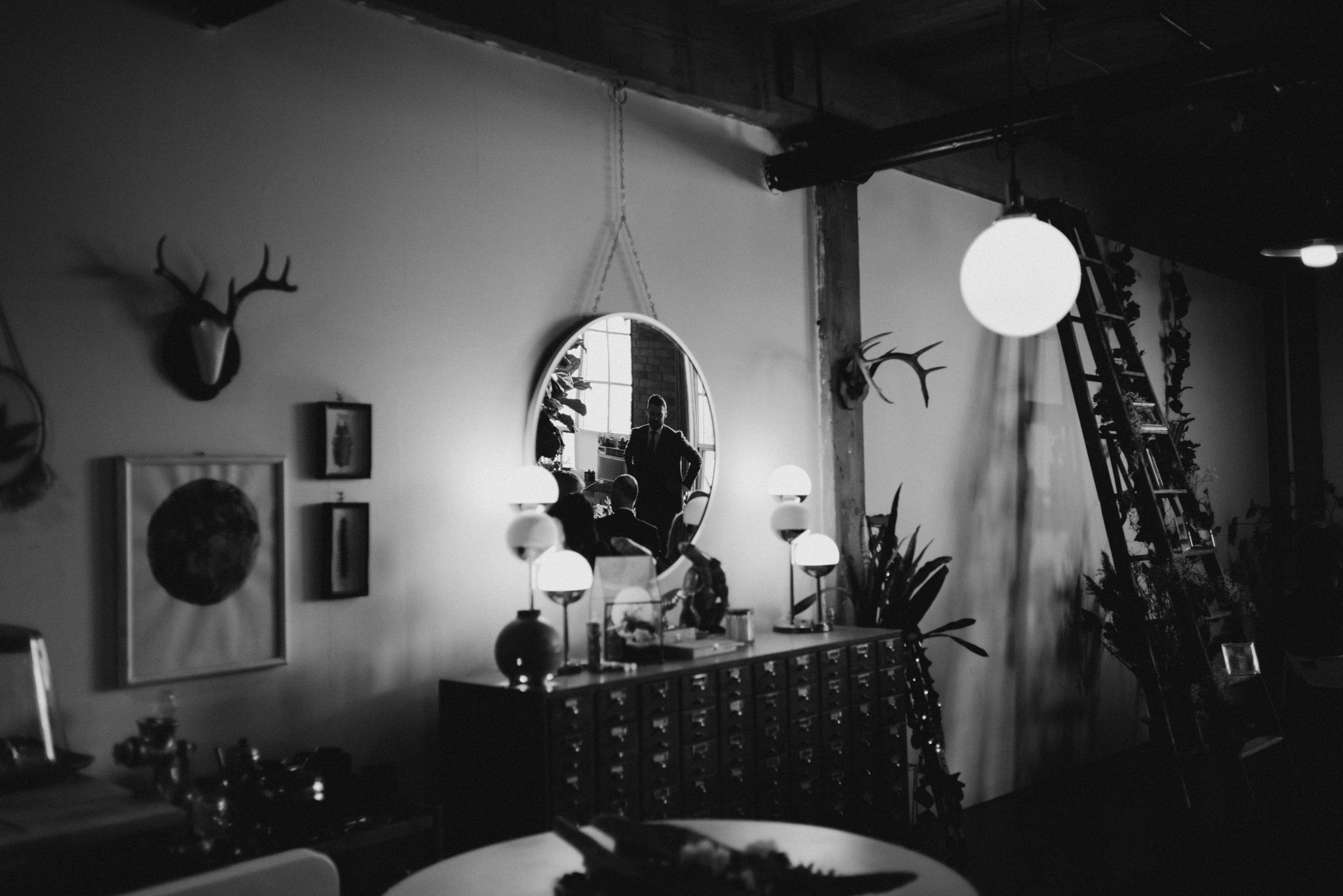 black and white images of groom in reflection of mirror in old loft apartment in Toronto