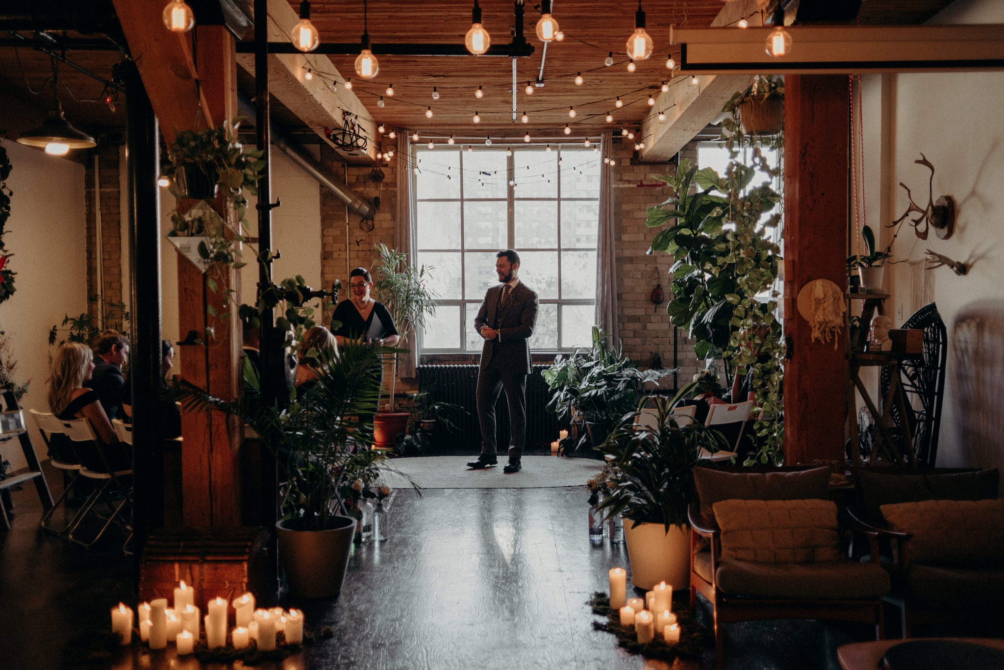 groom standing waiting for ceremony to start in old loft apartment in Toronto