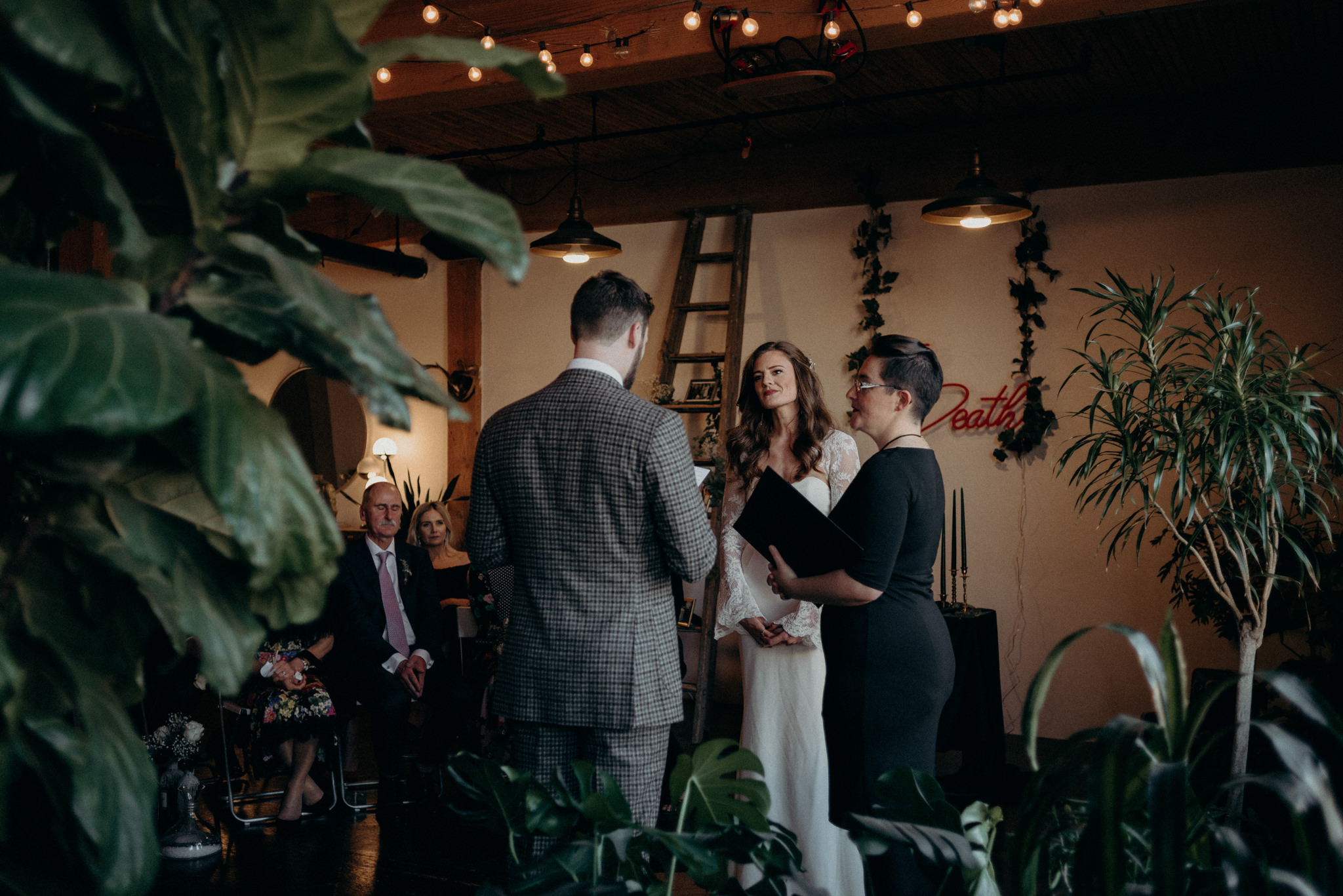 groom reading vows to bride surrounded by plants in old loft apartment, loft wedding in Toronto